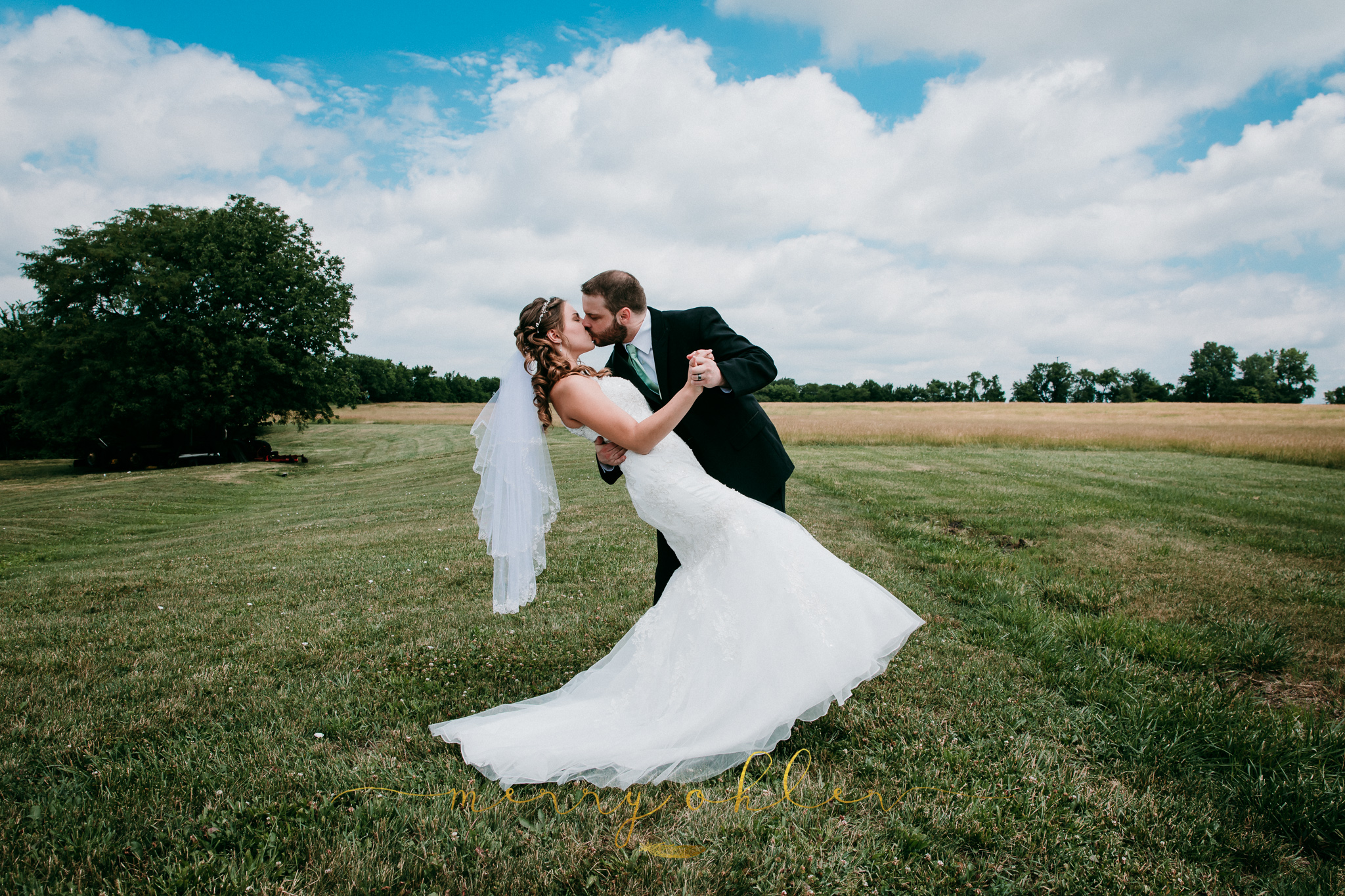 Groom dips bride and kisses her in wide open field under blue sky. © Merry Ohler Creative, 2019. Photo by Merry Ohler, who is the best wedding photographer in Kansas City.