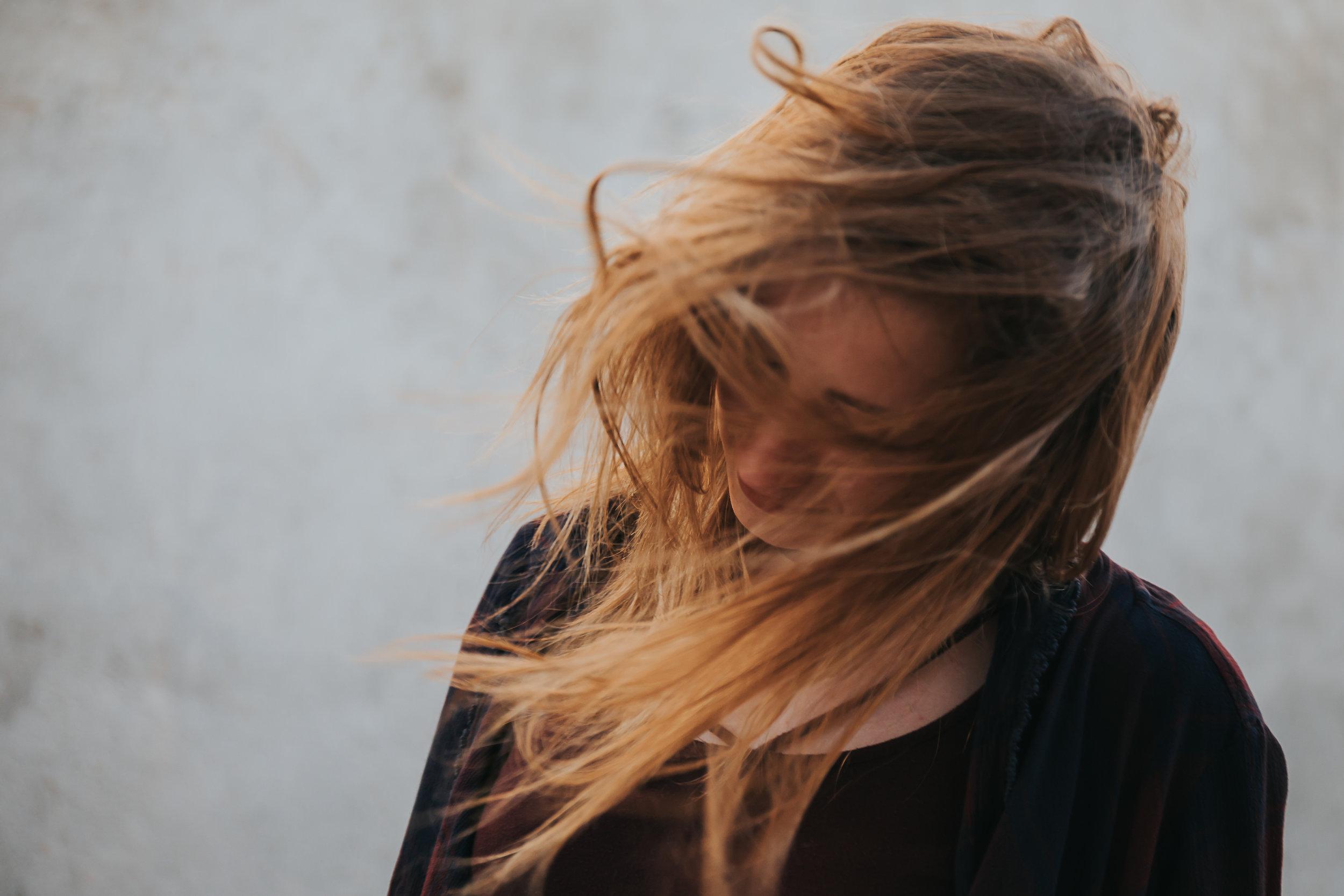 Teen girl's hair blows wildly in the wind. © Merry Ohler Creative, 2019. Photo by Merry Ohler, wedding photographer Kansas City.