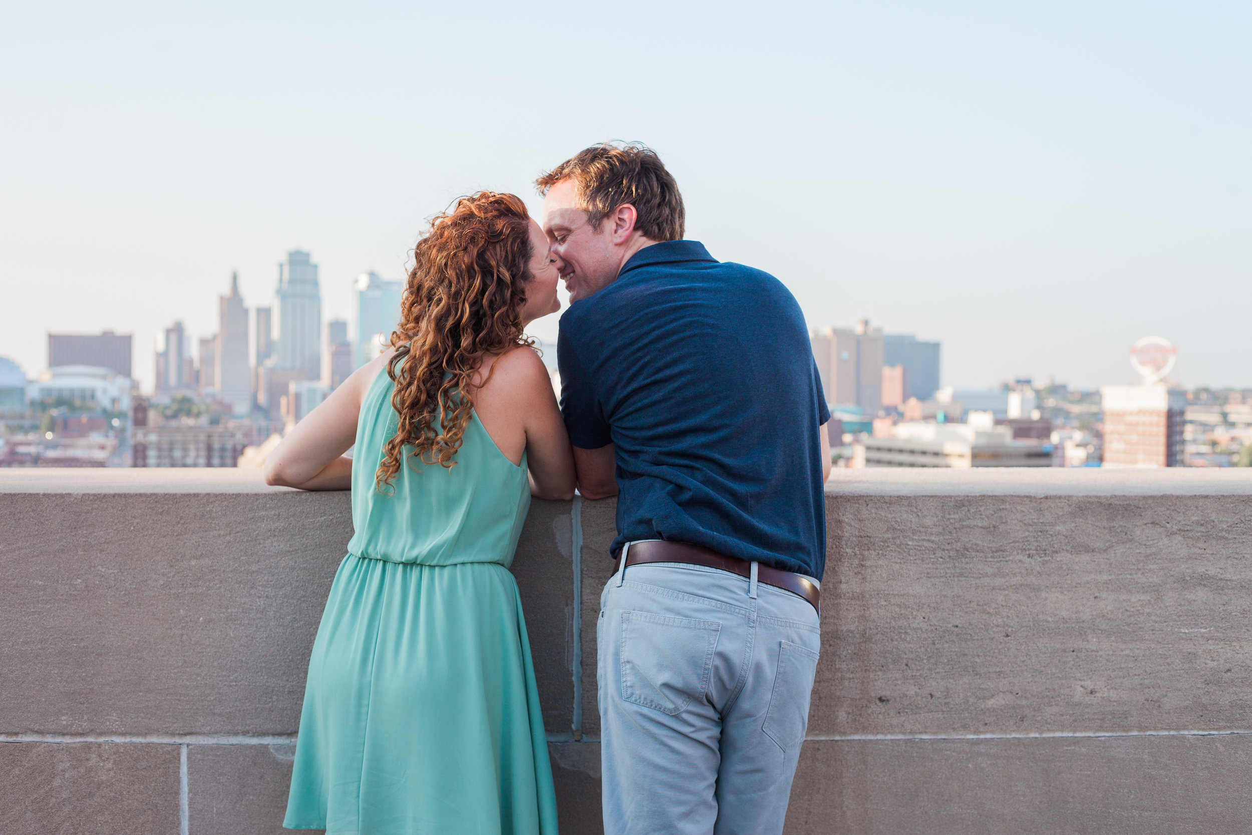 Attractive young couple kiss at Liberty Memorial overlooking the Kansas City skyline. © Merry Ohler Creative, 2019. Photo by Merry Ohler, who is the best wedding photographer in Kansas City.