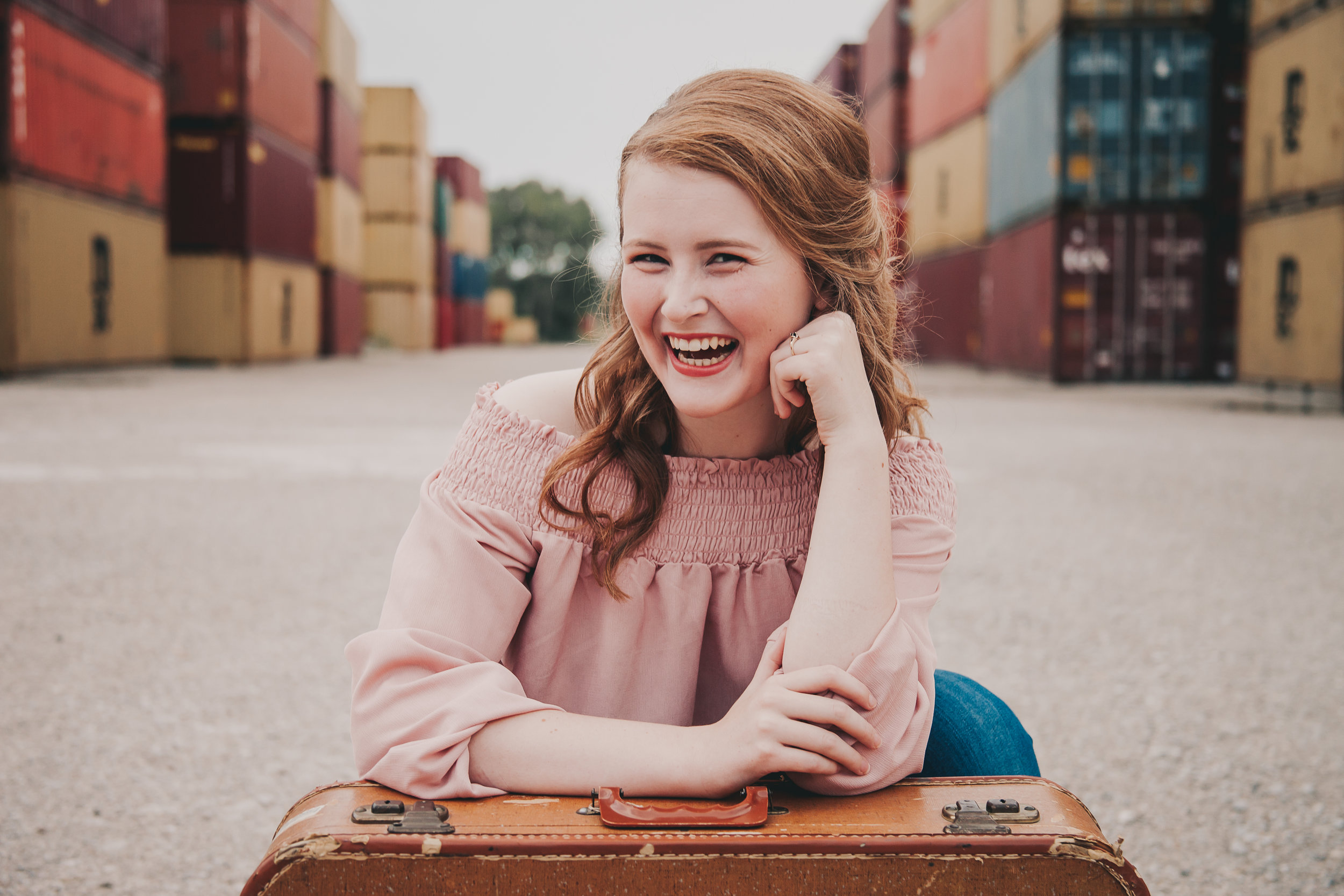 High school senior girl poses with vintage suitcase in front of colorful shipping containers. © Merry Ohler Creative, 2019. Photo by Merry Ohler, who is the best wedding photographer in Kansas City.
