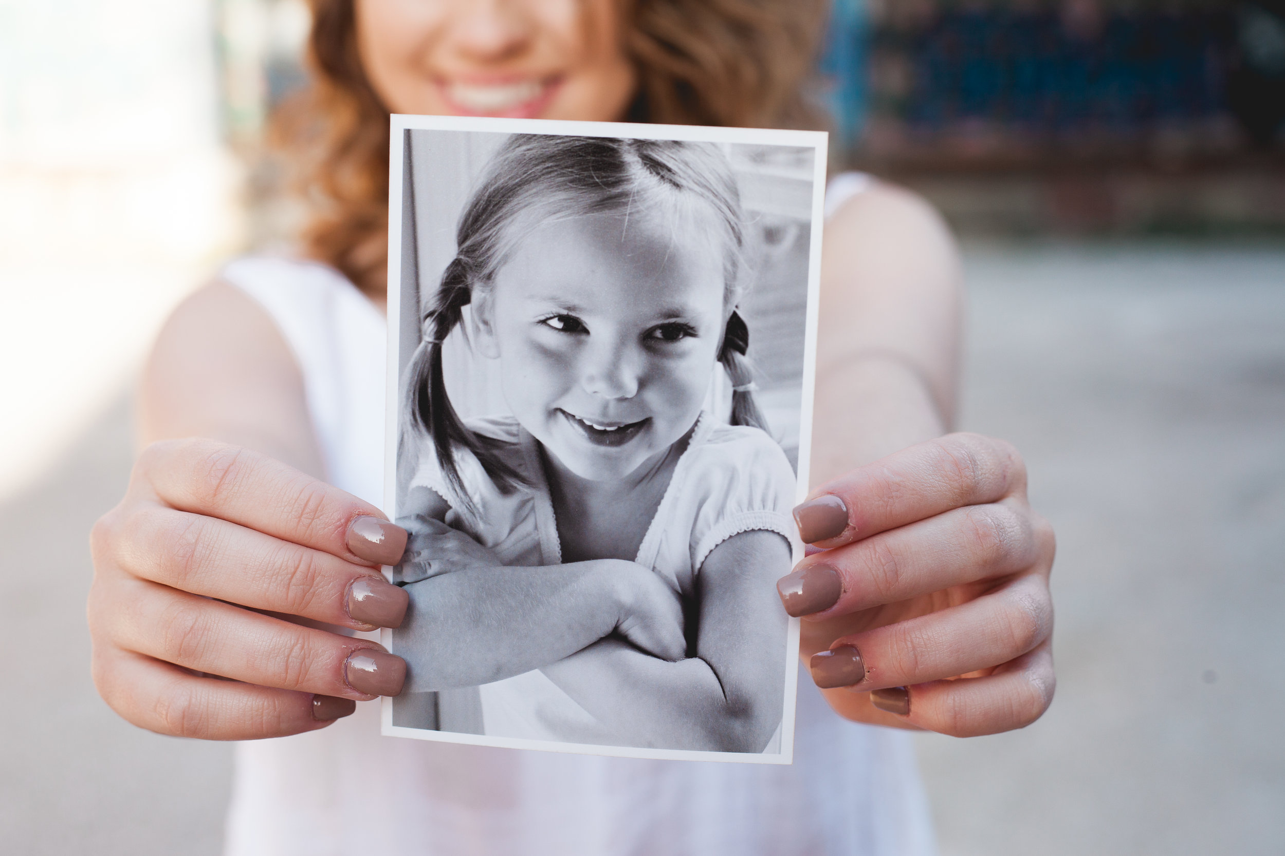 High school senior girl smiles in background as she holds a photo of herself from Kindergarten up as primary focus. © Merry Ohler Creative, 2019. Photo by Merry Ohler, Kansas City Wedding Photographer.