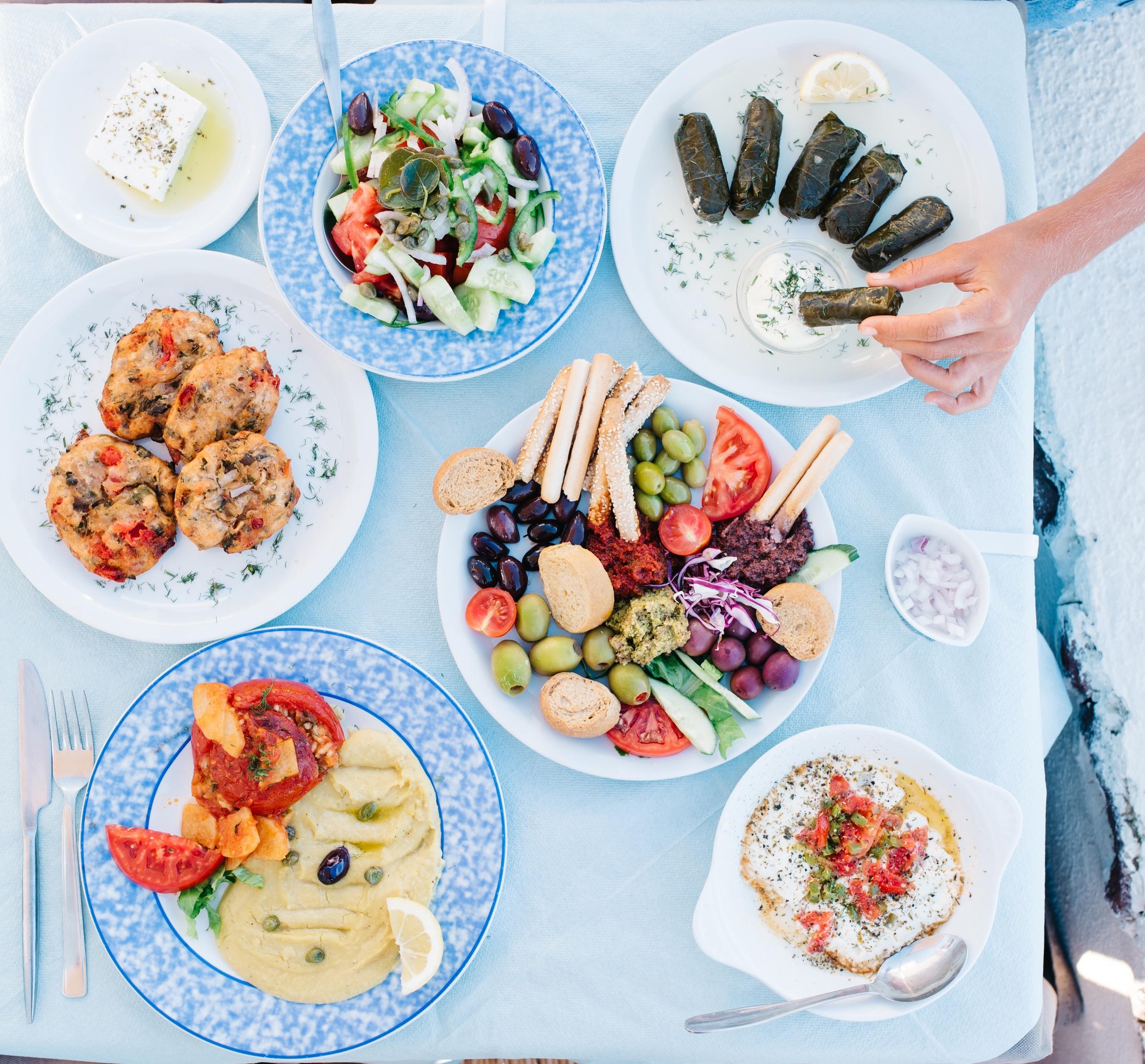 Greek spread: fava, tomato balls, feta, Greek salad, olive and dip plate, Dolmades, baked feta