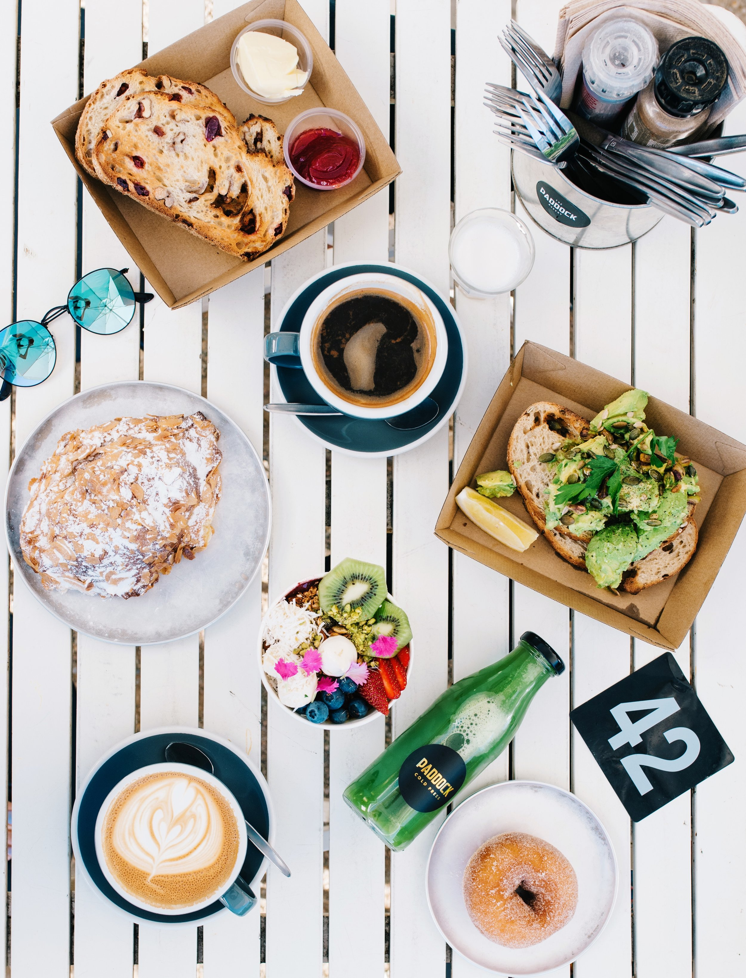 Top to bottom: cranberry walnut loaf, long black, almond croissant, avo toast, acai bowl, cold press juice, latte and donut