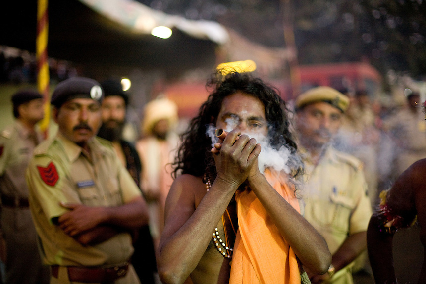 Police tolerates the use of Cannabis while a sadhu smokes in front of them, during Kumbh Mela.