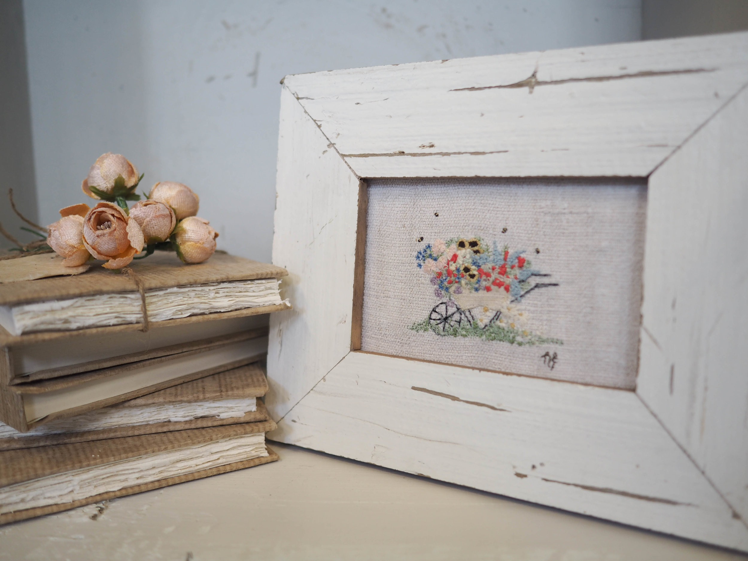 A stack of notebooks with beautiful handmade paper and my 'Day at the Allotment' embroidery framed with reclaimed wood.