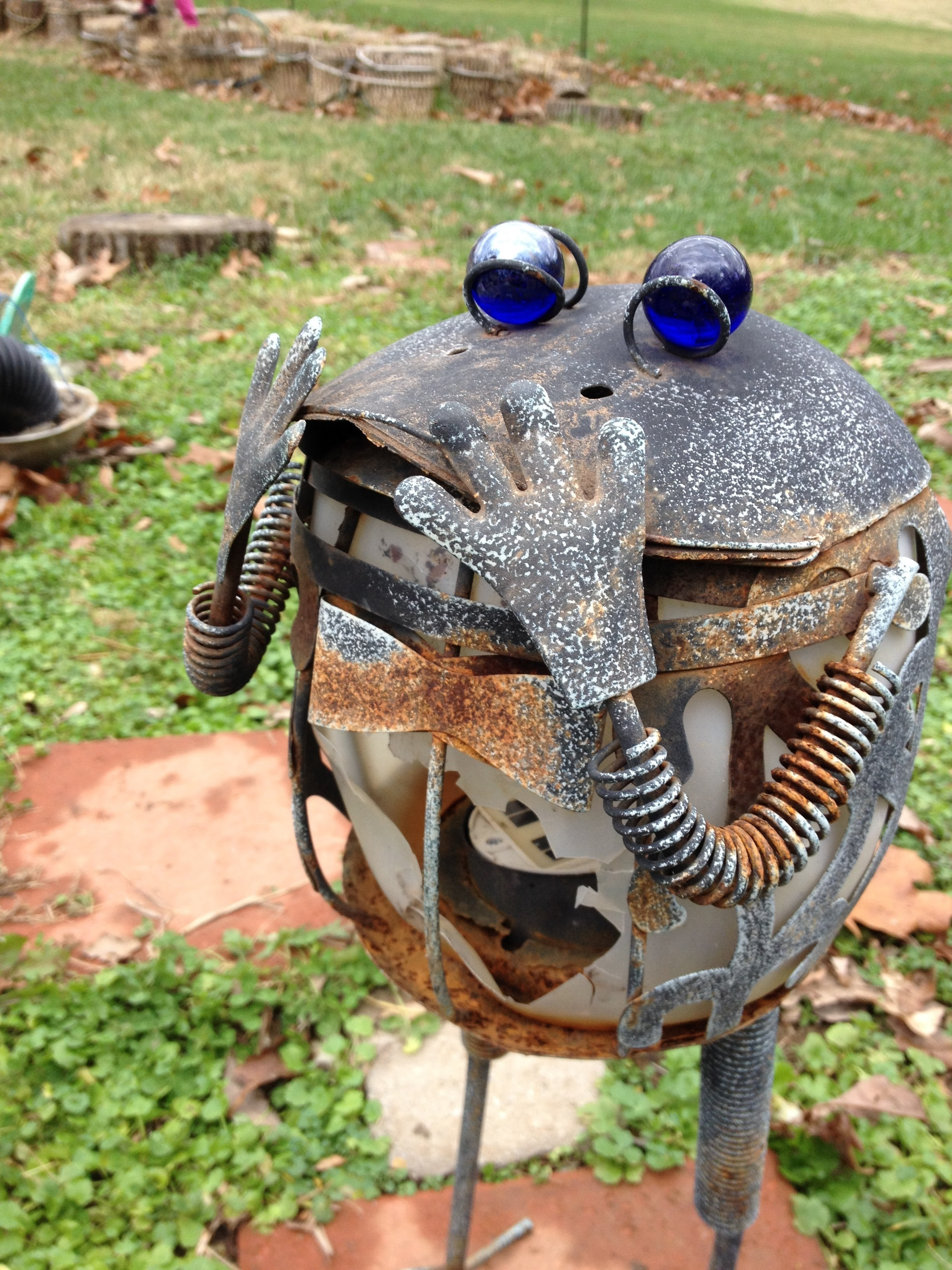 Frog statues in the garden aren't just cosmetic. They are light enough that almost any student can pick them up and move them. Being encouraged to decorate the garden before or after tending to the plants can engender a feeling of attachment to the garden and the plants therein.