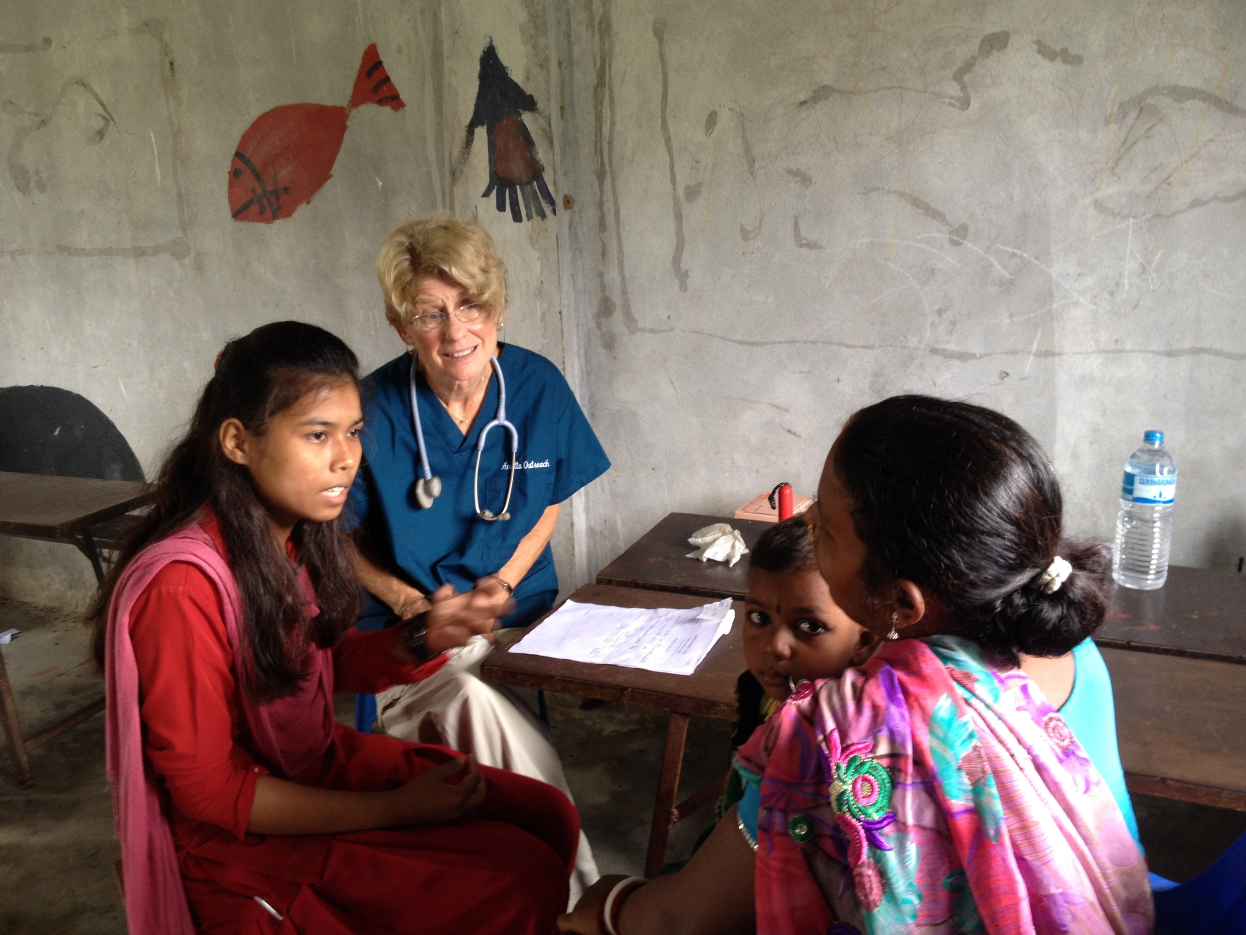 Dr. Joyce Duncan, assisted by Dhamma Binna, one of our first auxiliary nurse midwife nuns, examining a village mother and baby. Anatta Medical Clinic 2014