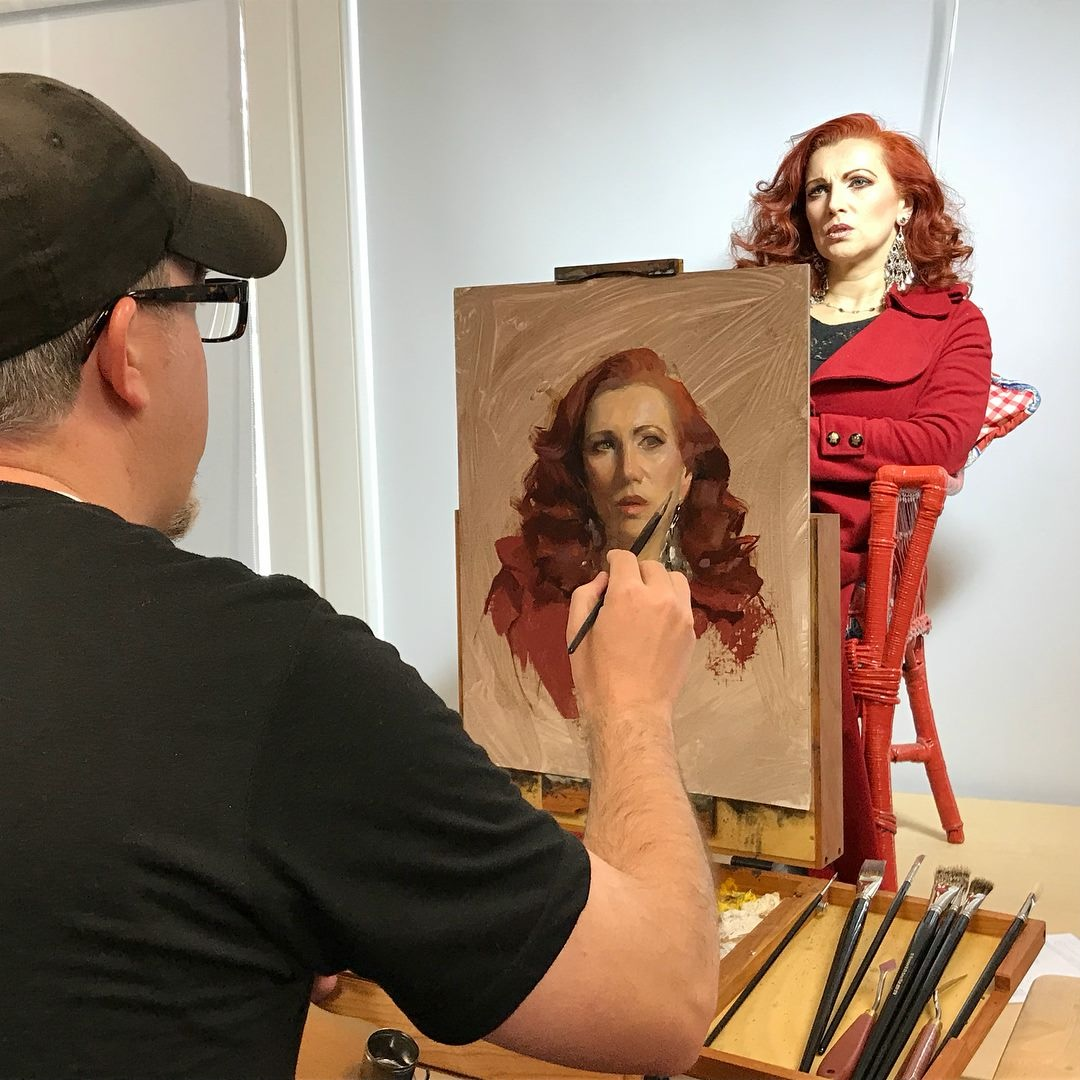 Casey demonstrating his process of painting a portrait during a workshop.