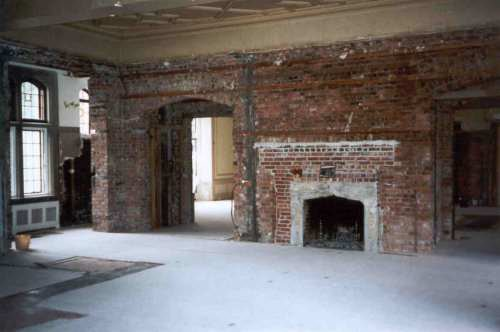 This is the same room, from about the same point of view, with the walls and false ceiling taken out and the floor covered. Note how the original fireplace had been bricked in and made much smaller.