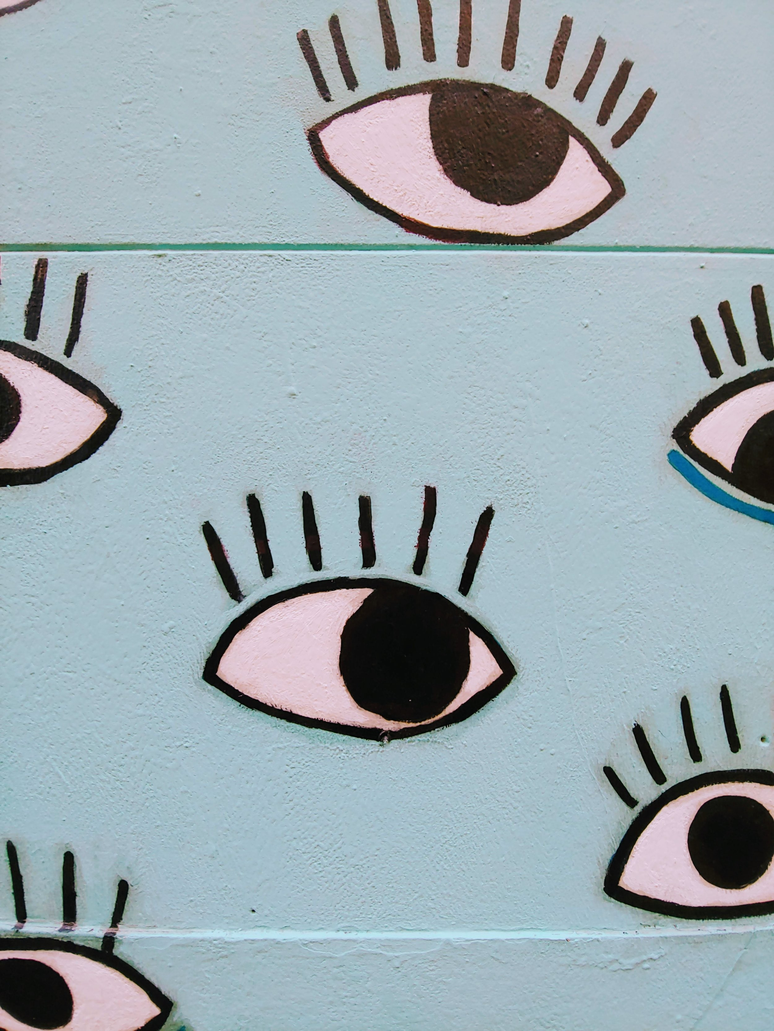 Photo by  erika akire  on  Unsplash . A light blue wall with cartoonish eyes painted on it.