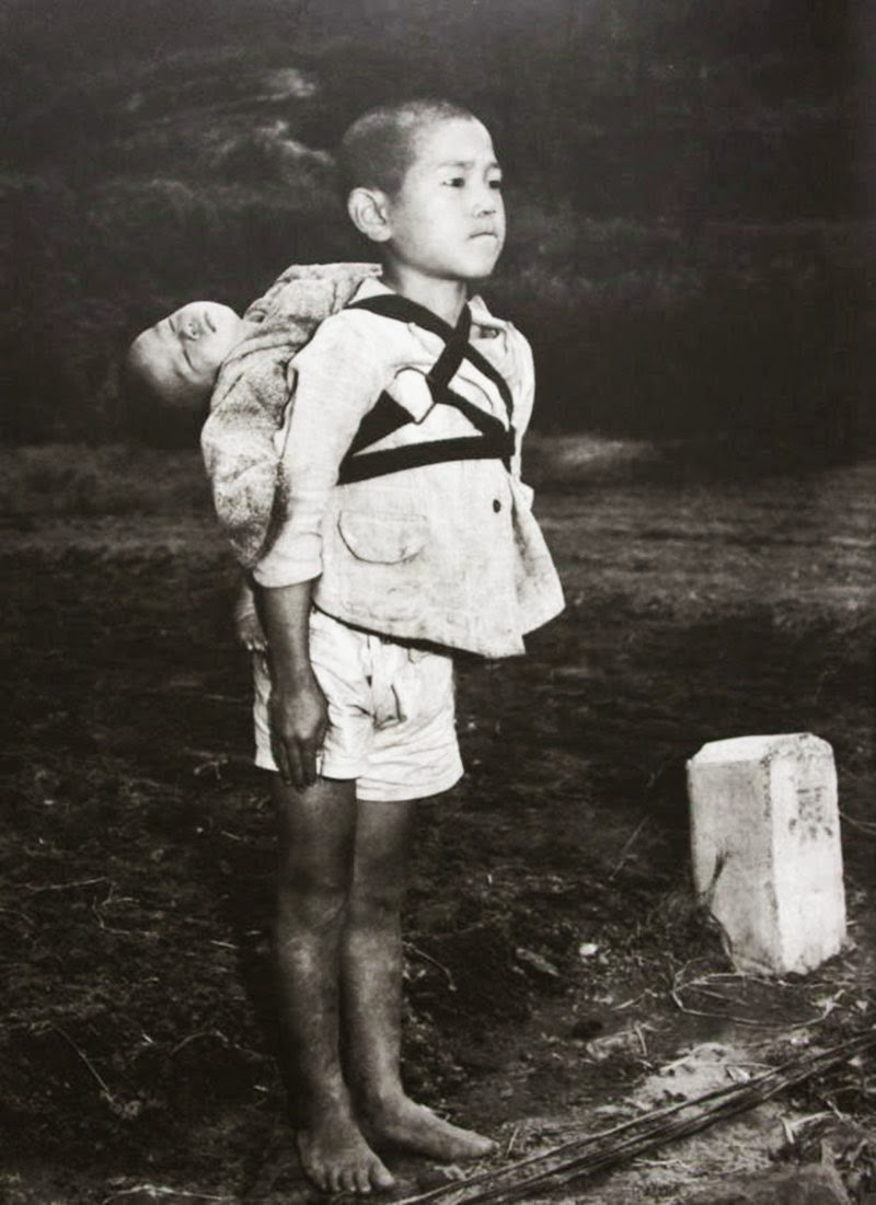 NAGASAKI, 1945 - A Japanese boy standing at attention after having brought his dead younger brother to a cremation pyre, 1945