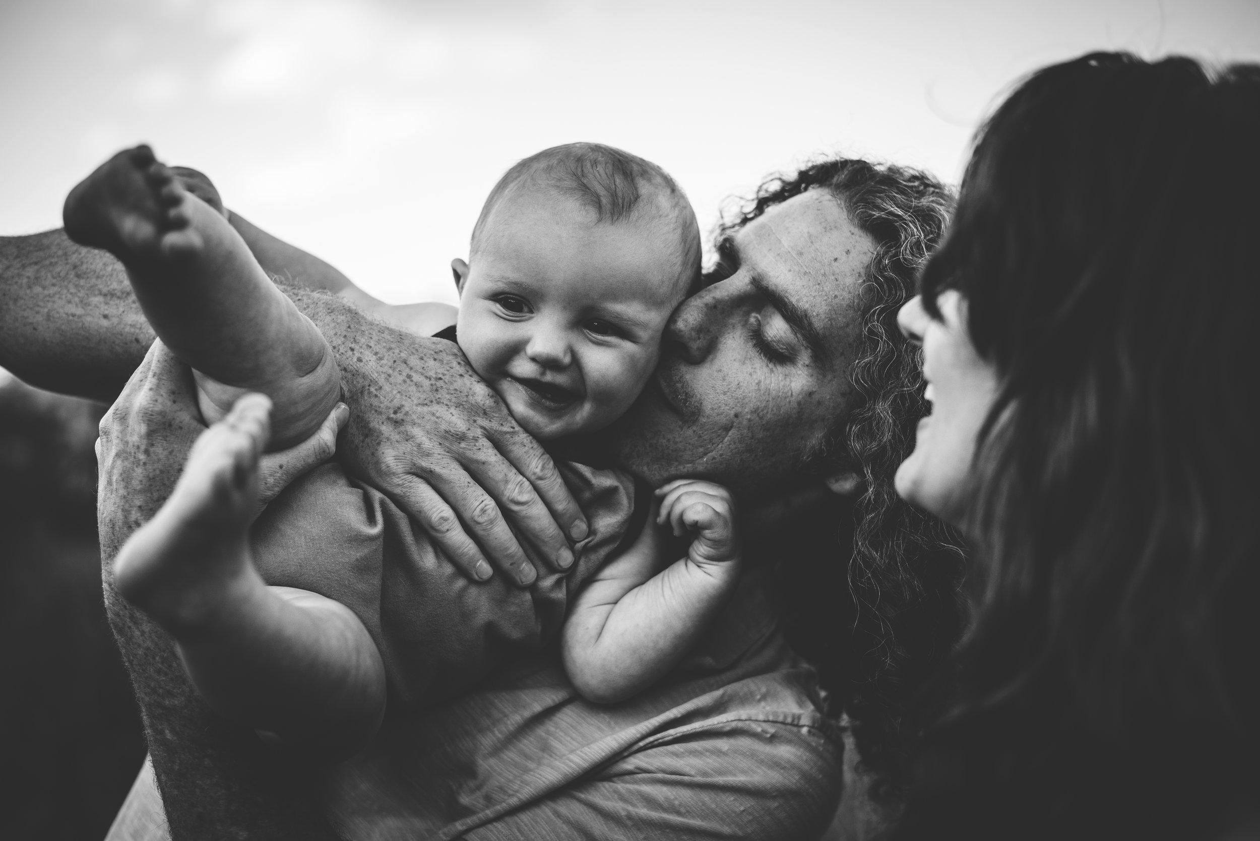 Mom and dad snuggle their son in Garden of the Gods photography session in Colorado Springs.