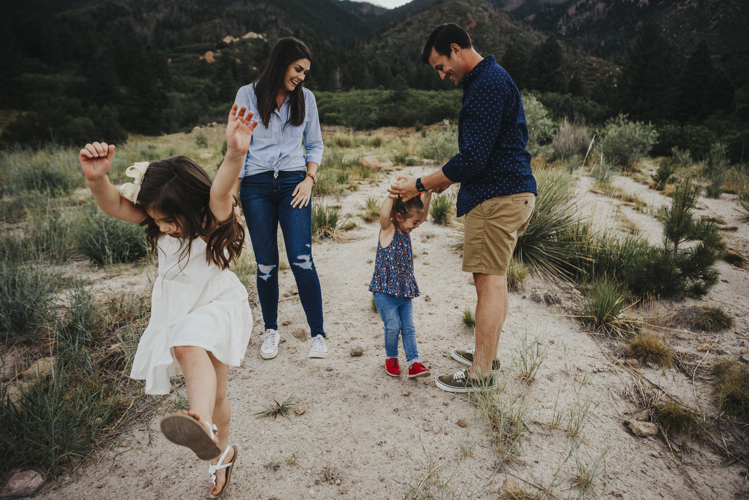 Kids jump and play during family session with mountain views in Colorado Springs.