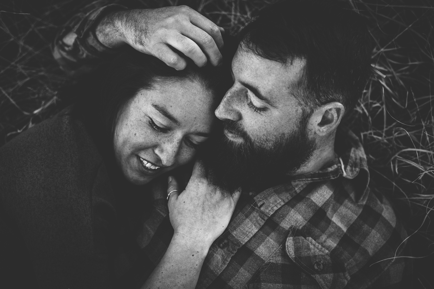 Couple snuggle while laying in mountains in Colorado Springs engagement session.