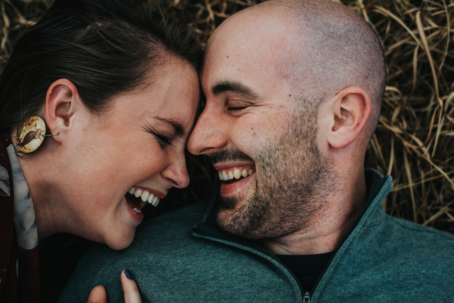 Couple laughing during snuggle engagement session in Colorado Springs mountains.