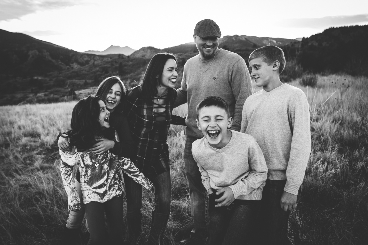 Large family laughs and plays during their family session in the foothills of Colorado Springs.