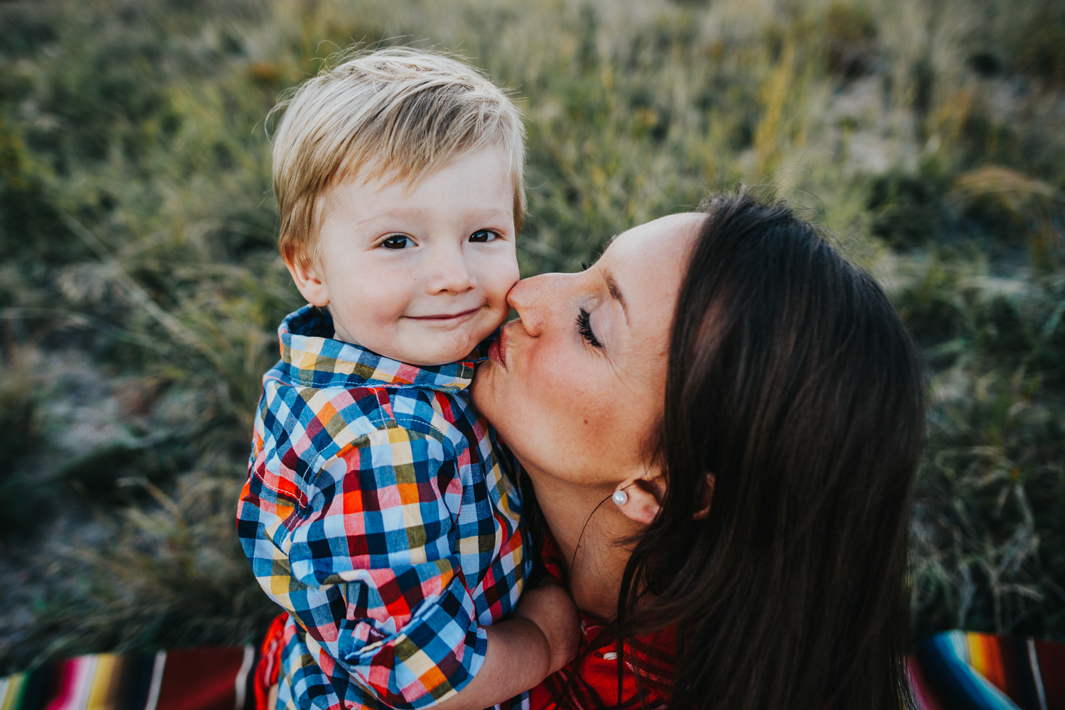 Little boy snuggles with his mom during a family session in Colorado Springs open space.