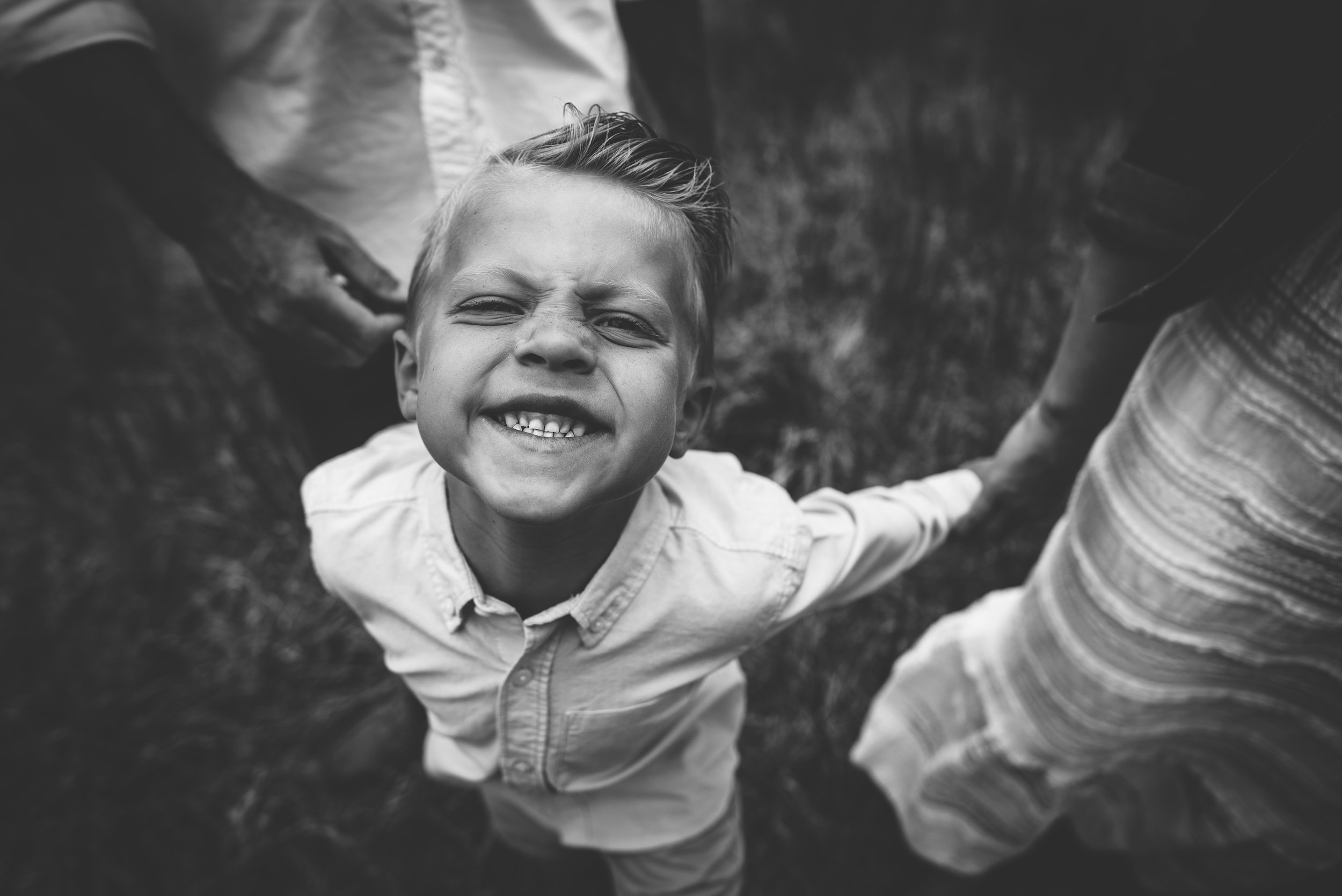 Little boy makes a silly face with his family in Colorado Springs during family photo session.