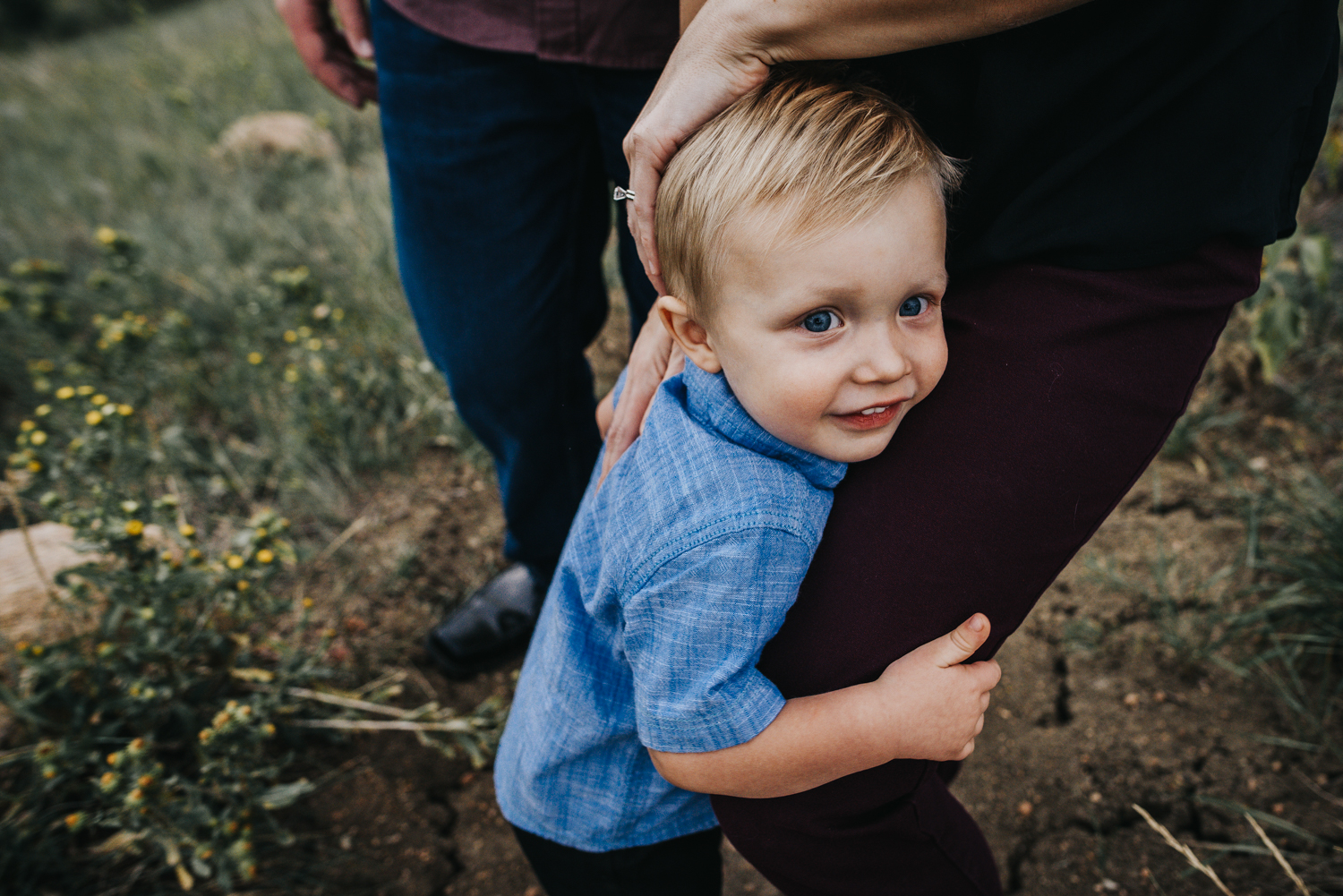 Little boy snuggles on his mama's leg during a family photo session in the mountains in Colorado Springs.