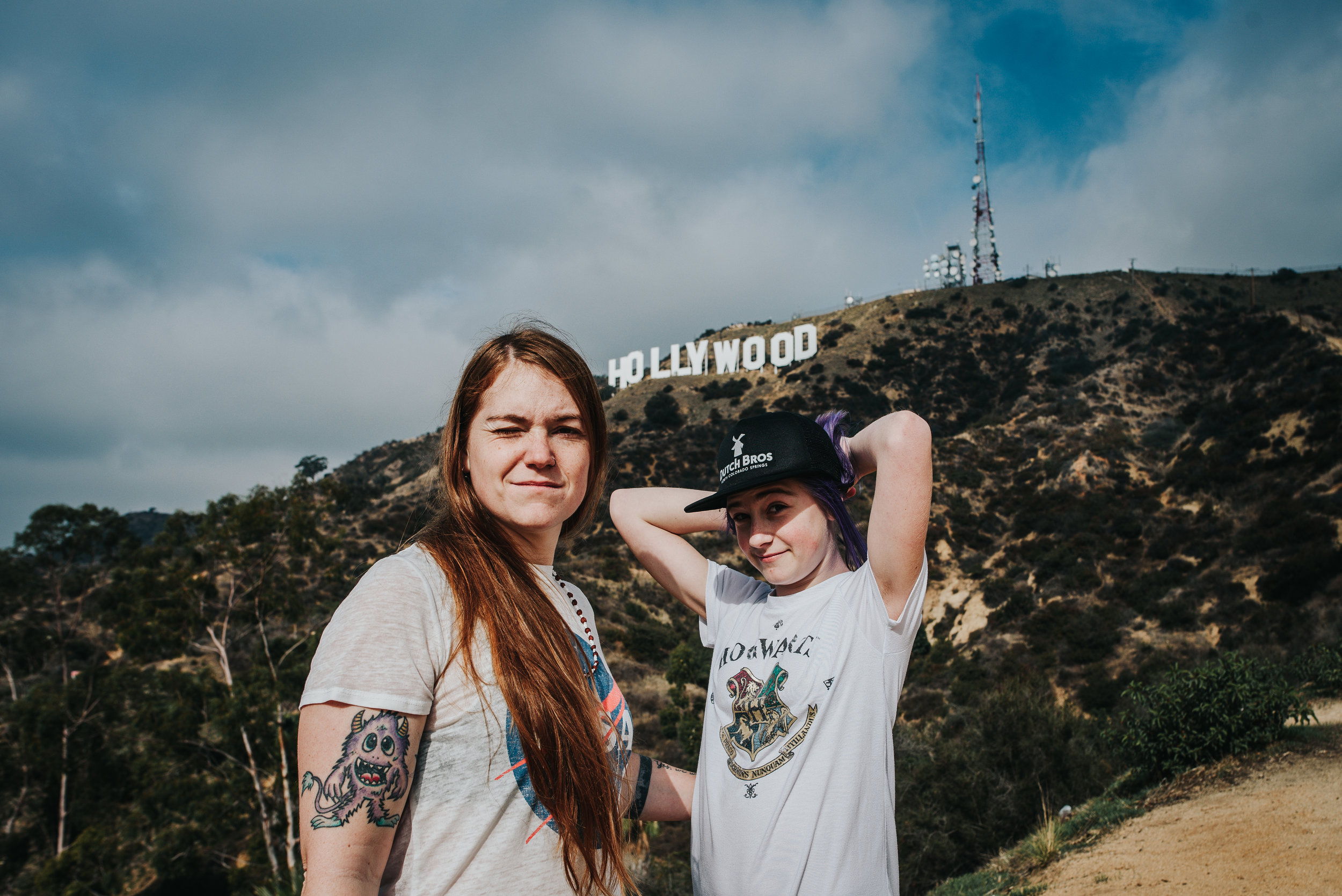 Mother and daughter pose in front of Hollywood sign in California.