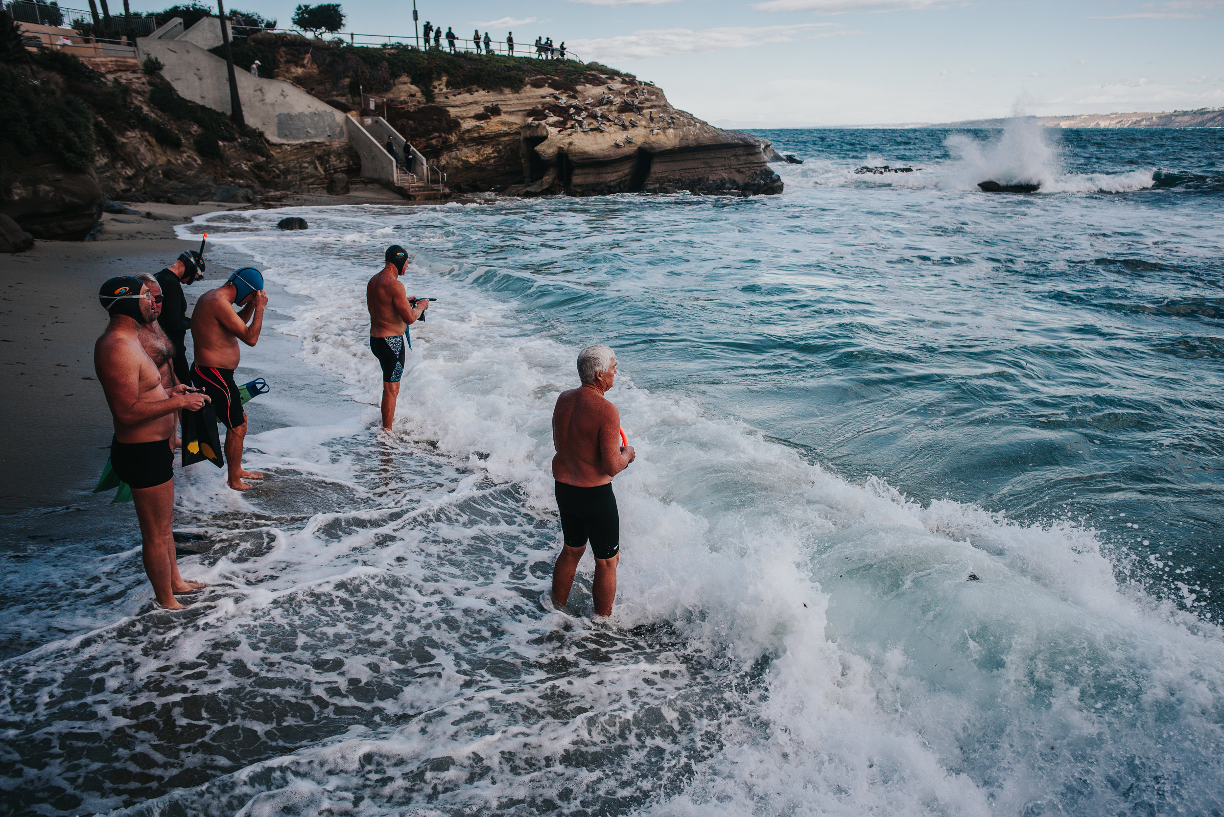 Older men brace the fierce California surf.