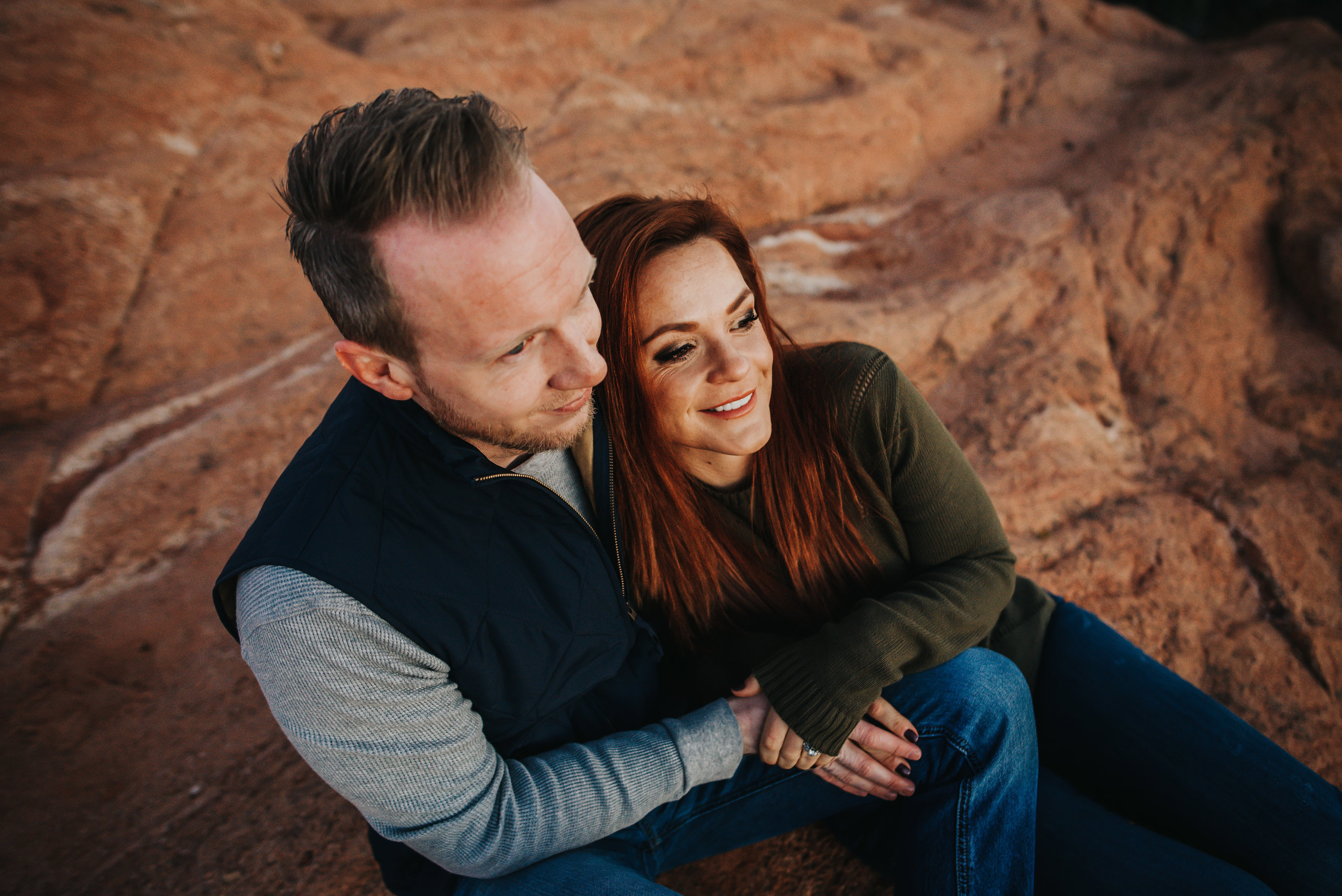 Couple snuggles at Garden of the Gods Park in Colorado Springs during photography session with Wild Prairie Photography.