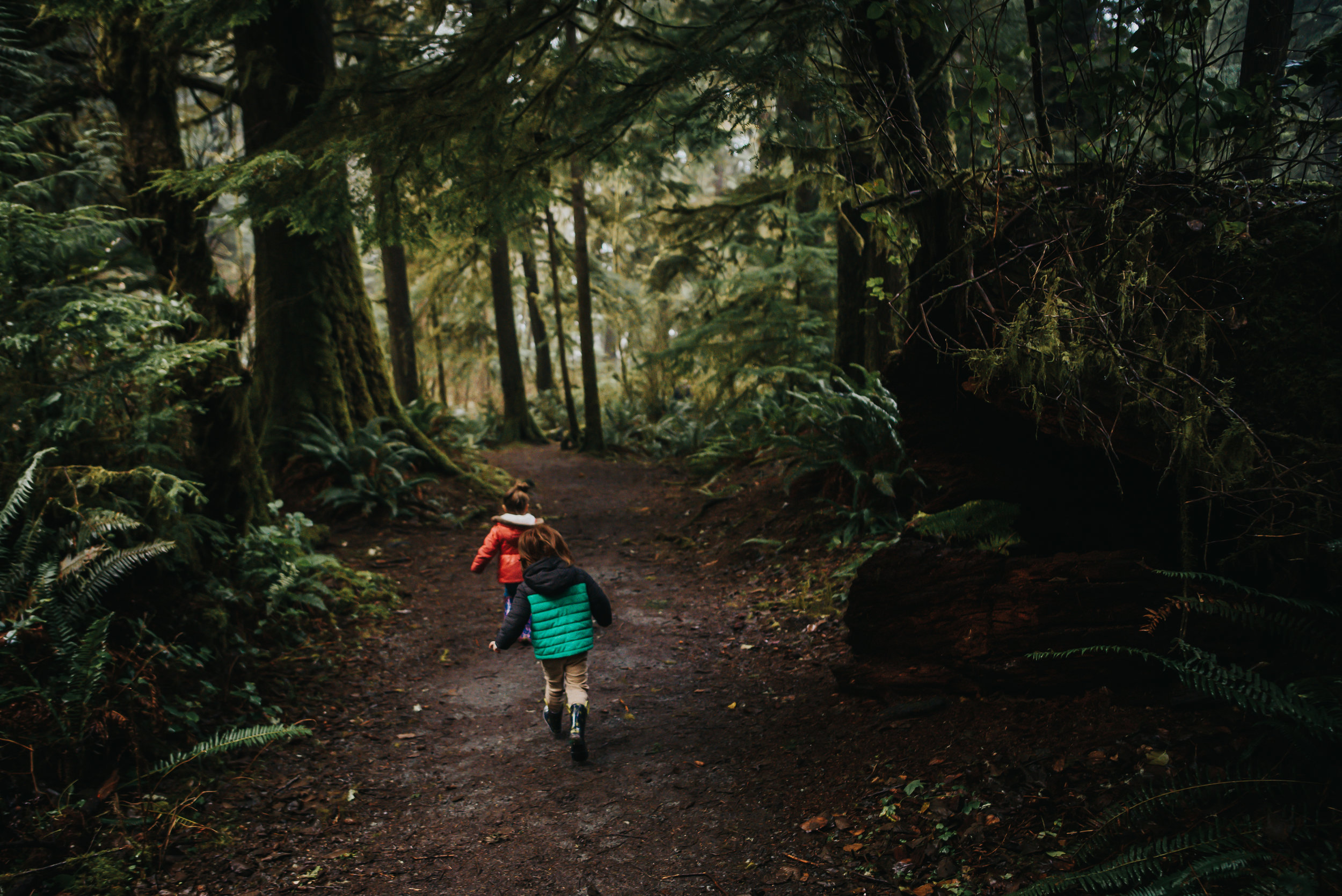 Twins play in the forest on trek down to the pacific coast in Oregon.
