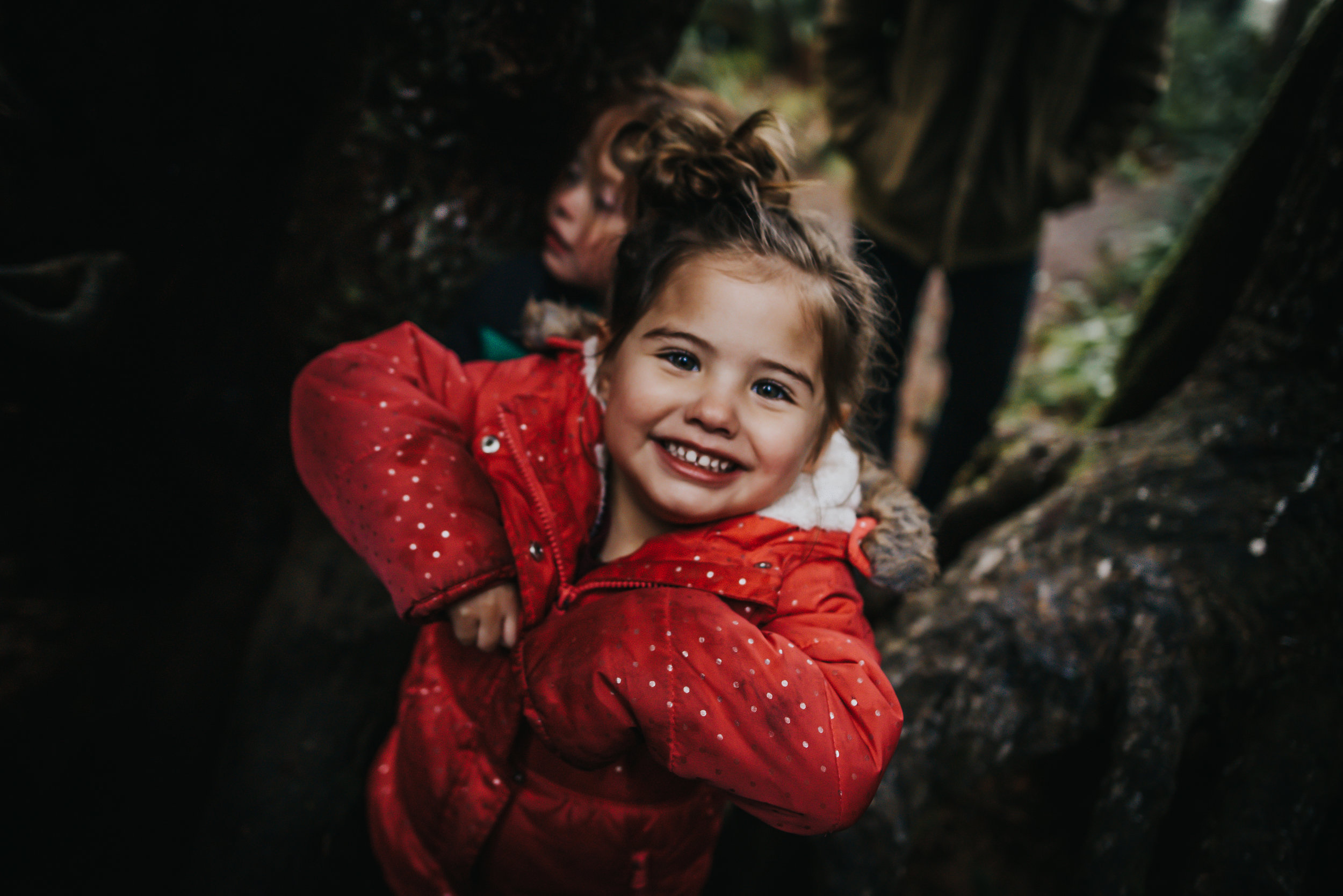 Little girl smiles and is enjoy her time in a tree in Oregon at Oswald West State Park.