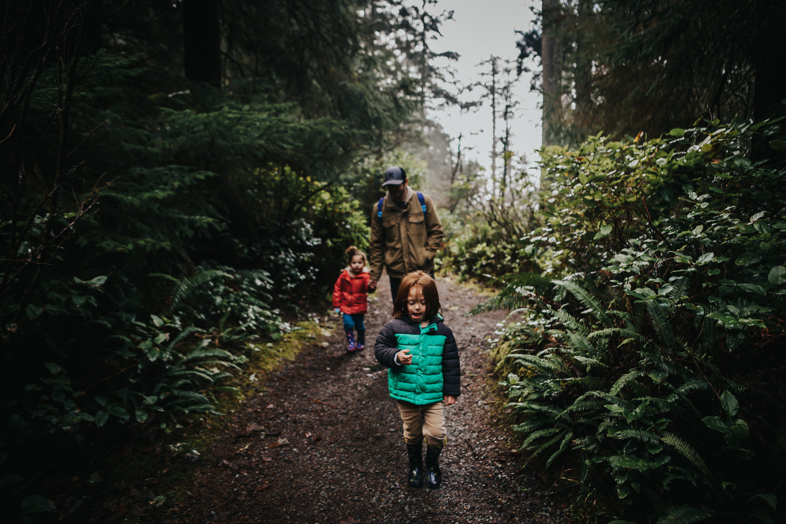 Children walk with their dad in the Oregon Forest in Oswald West State Park.