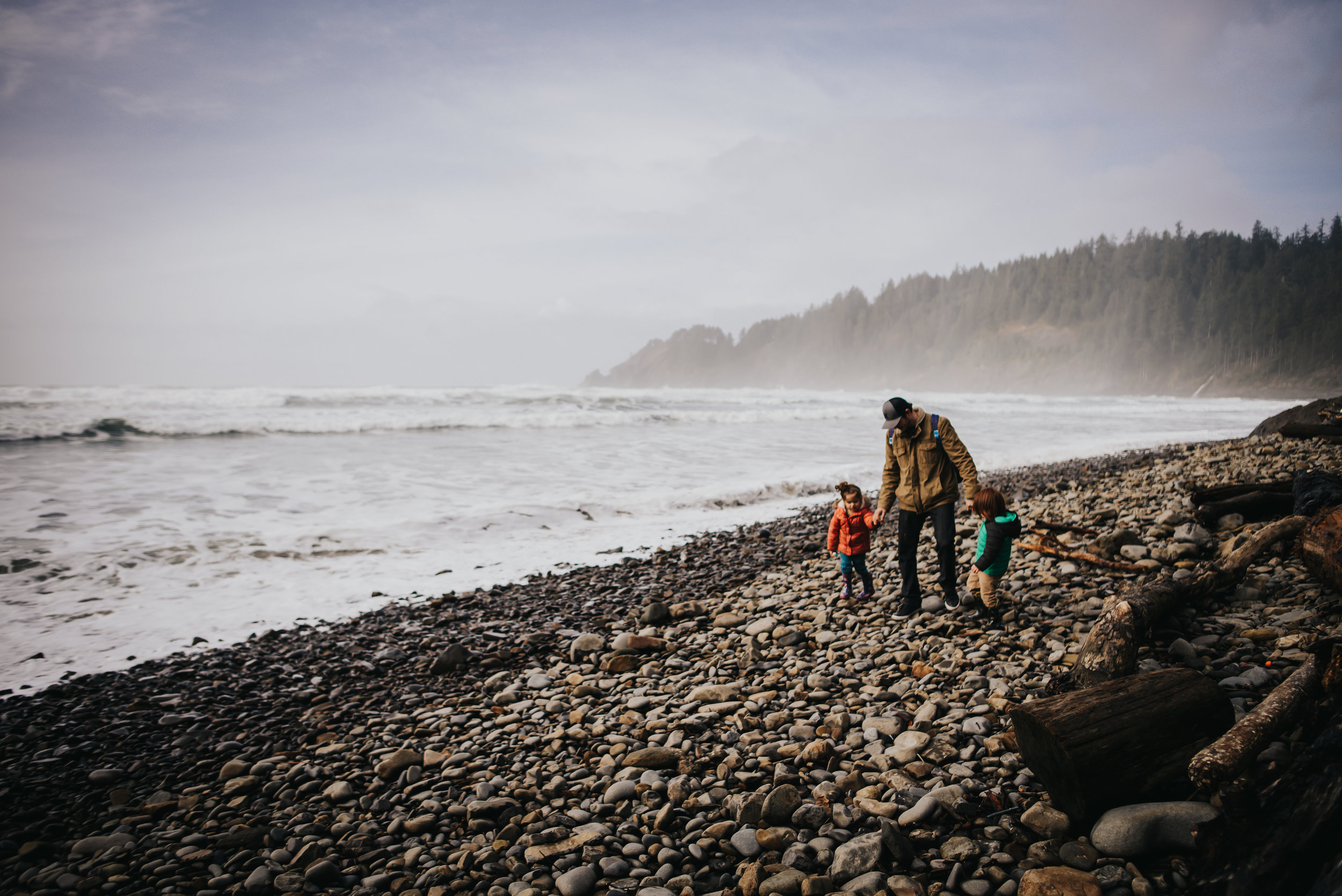 Father and his children walk along the coast in Oregon.