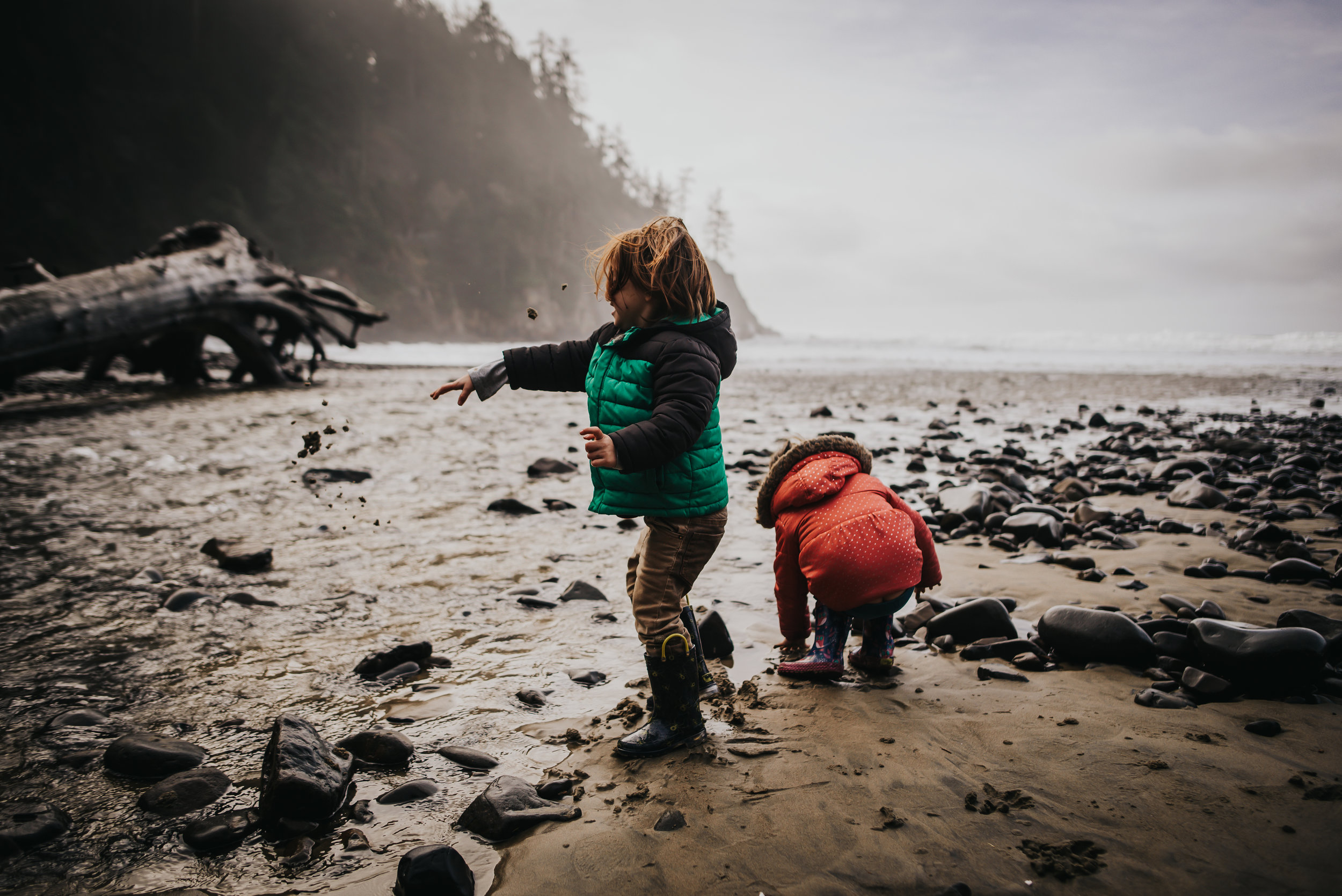 Little boy and his sister throw rocks and sand during trip to the Pacific Coast.