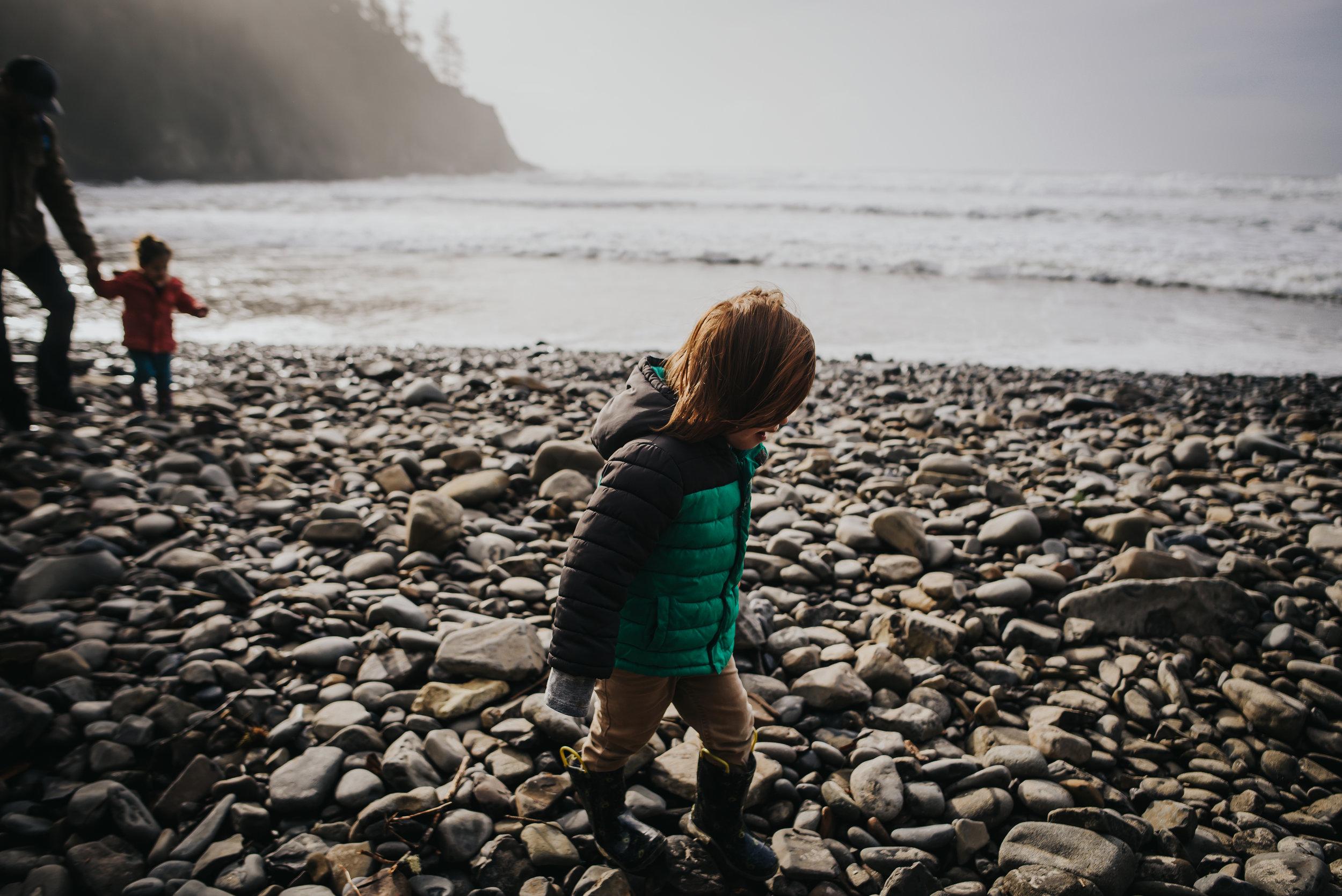 Little boy hikes on rocks near the ocean in Oswald West State Park.