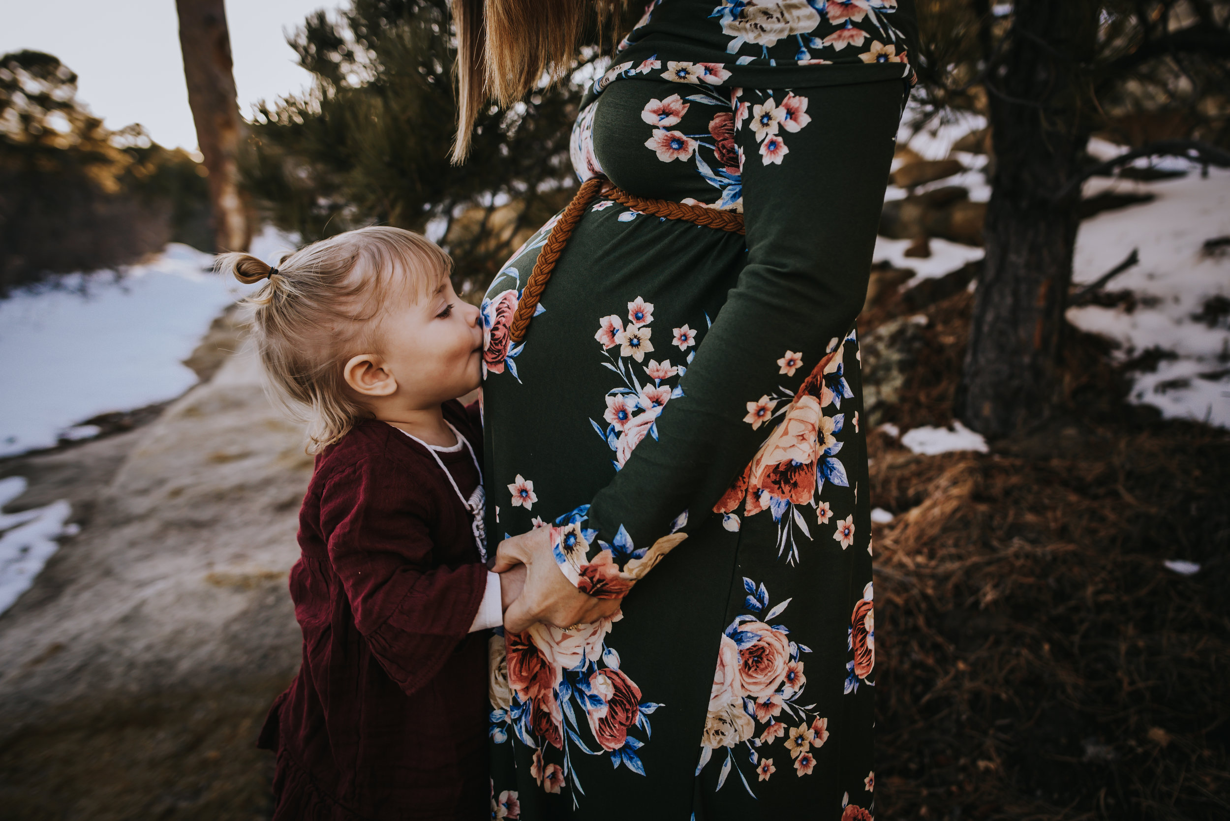 Little girl kisses the pregnant belly of her mother during a maternity family session in Colorado Springs.