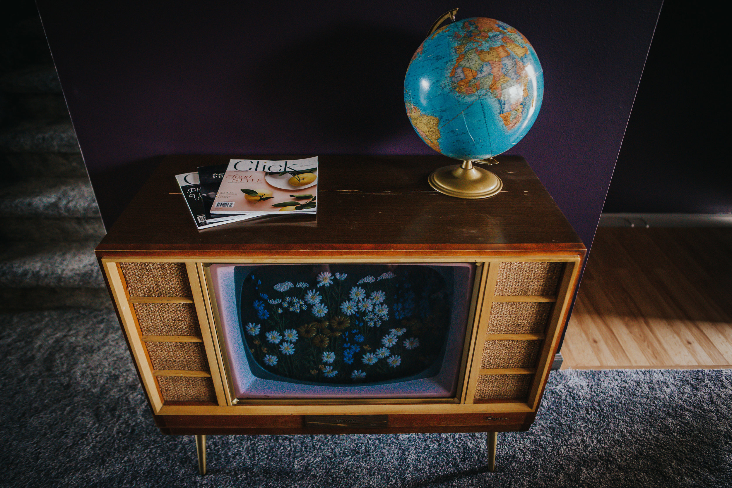 Vintage television set with flowers and magazines.