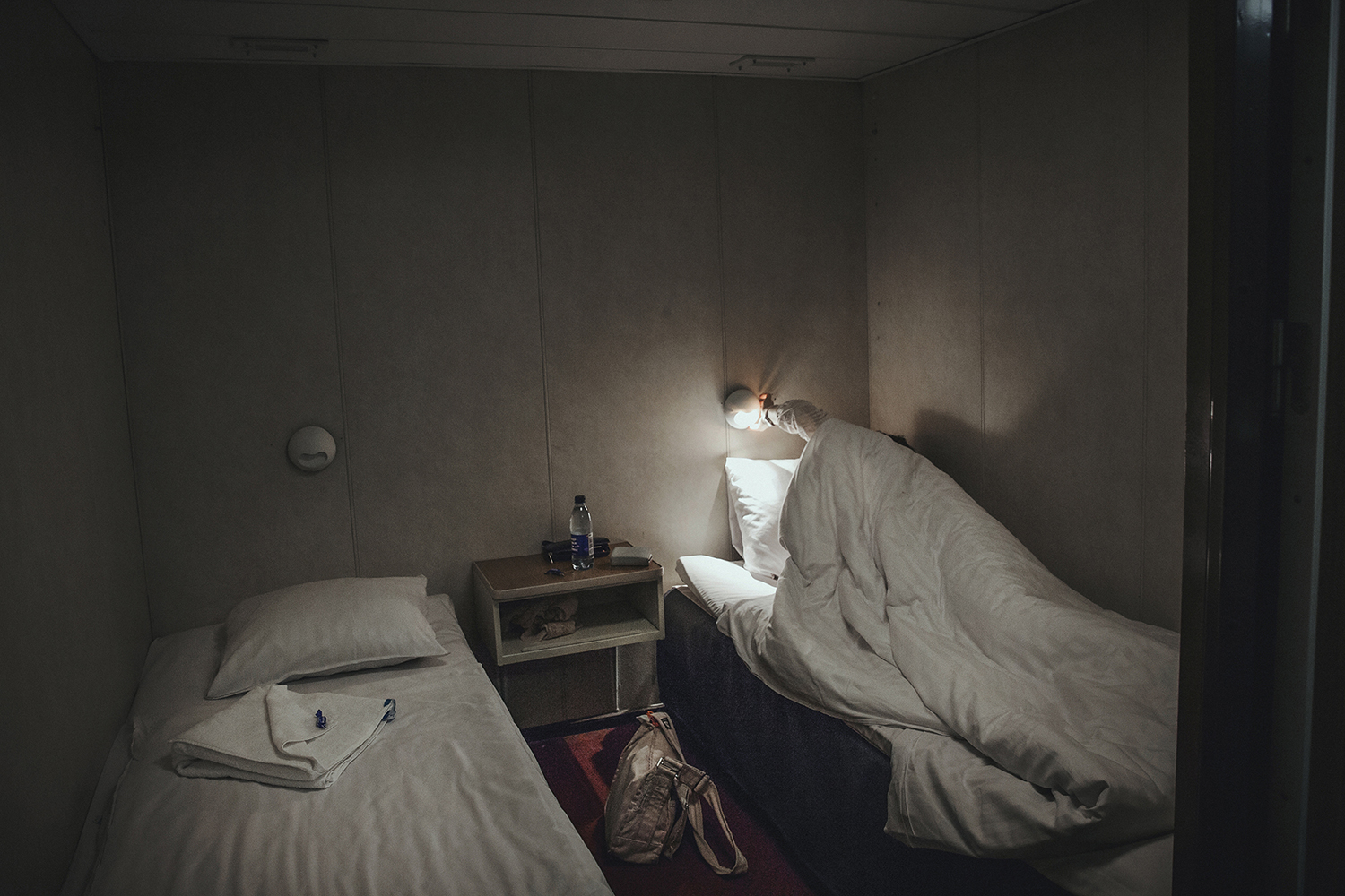In the dark of the cabin, Carola goes to rest during the journey over the sea.