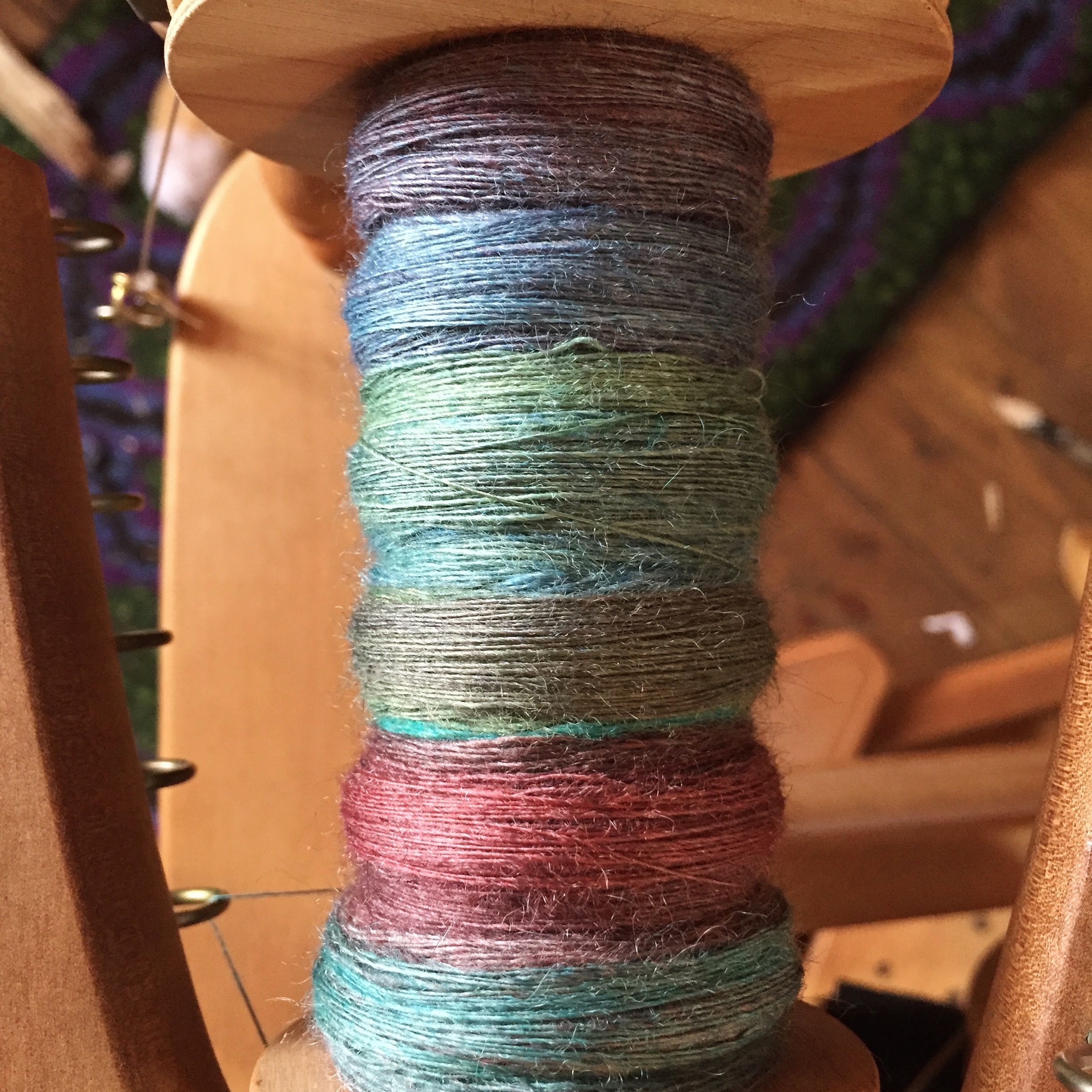 Multi coloured hand dyed yarn on the bobbin of a spinning wheel