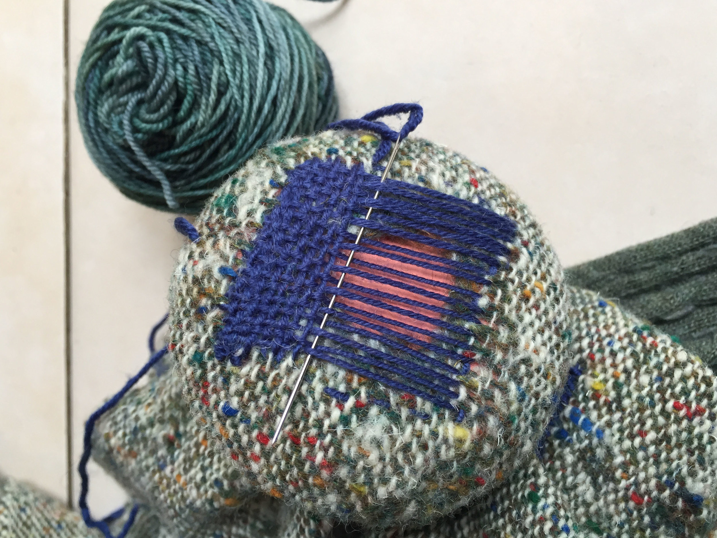 Blue woven darn in process on hand woven fabric