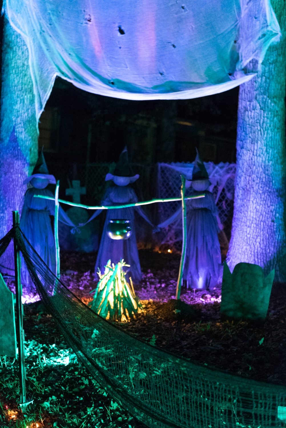 A closer look at the  step-in fence posts . I painted them with black spray paint and draped spooky cloth between them to make a fence! Fire and ice lights projected onto white gauze adds a cool moving light effect. I cut holes into the cloth so the wind will move freely through it, but left the ends loose so they would blow in the breeze for a more haunted look!