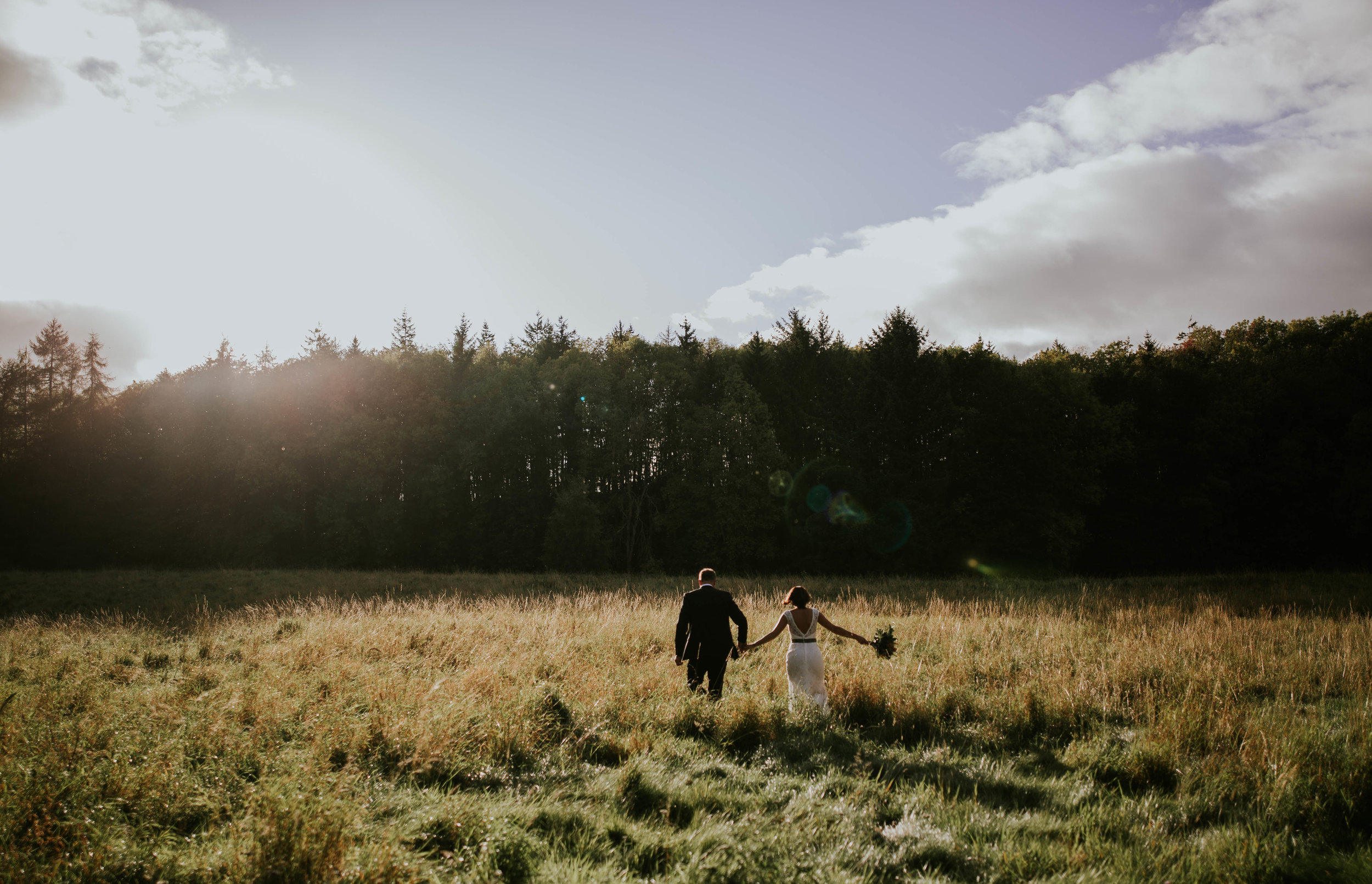 Bride and groom are walking on the Dalhousie fields.