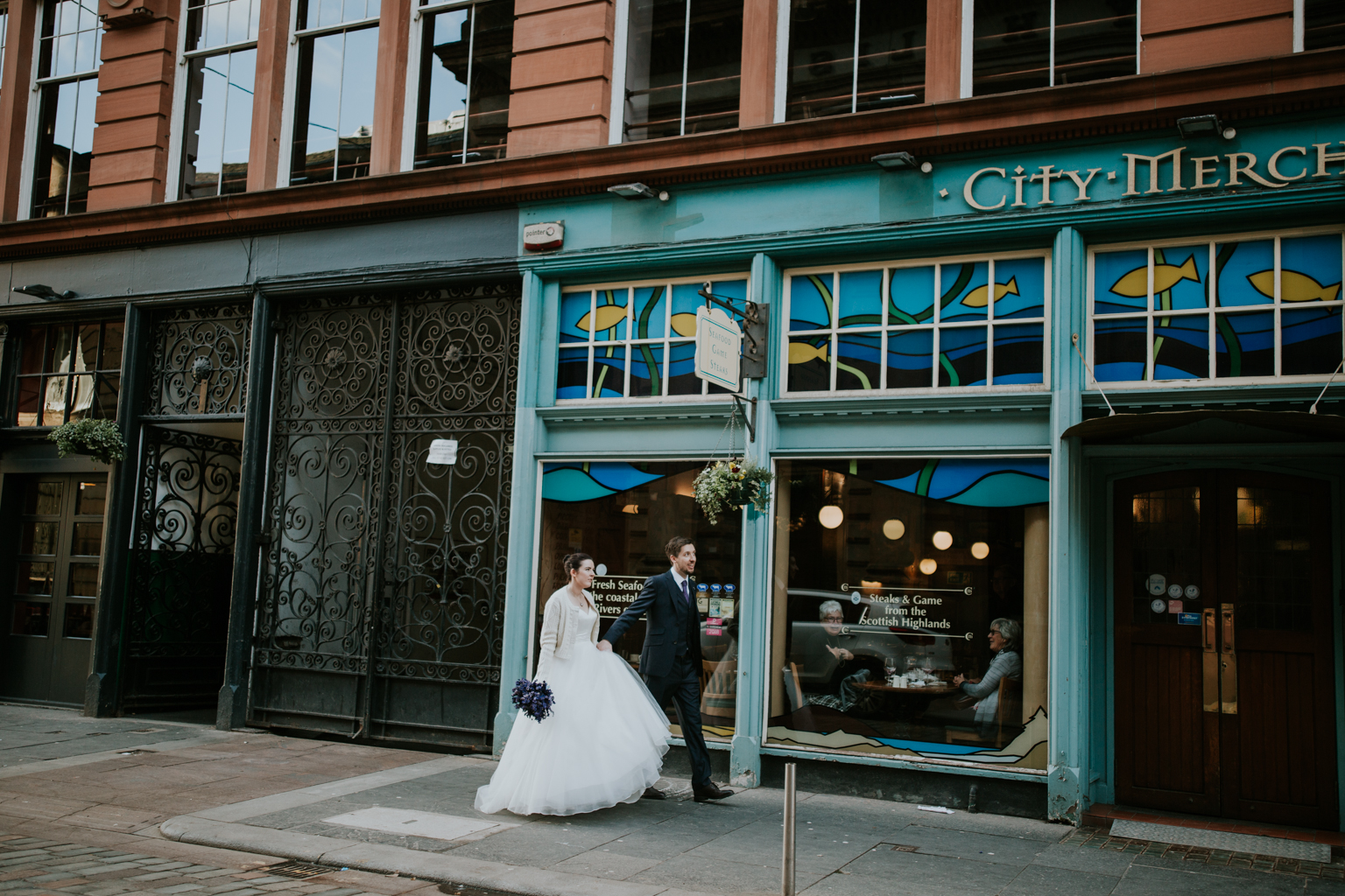 Bride and groom are walking in the Merchant city of Glasgow