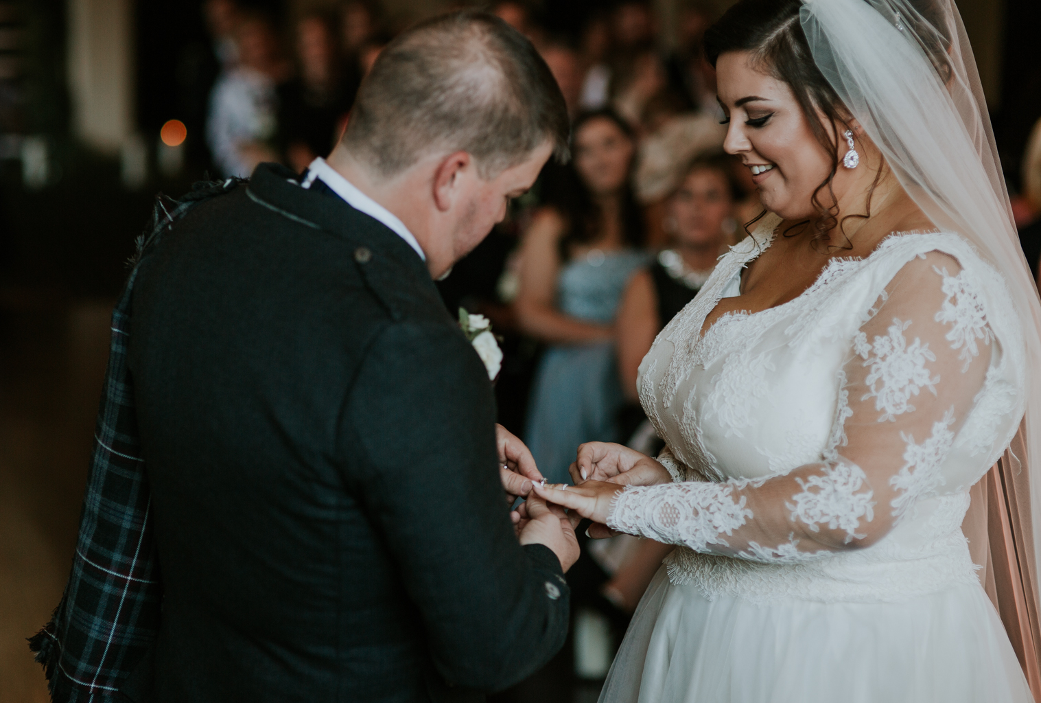 Groom putting the wedding ring on bride's finger