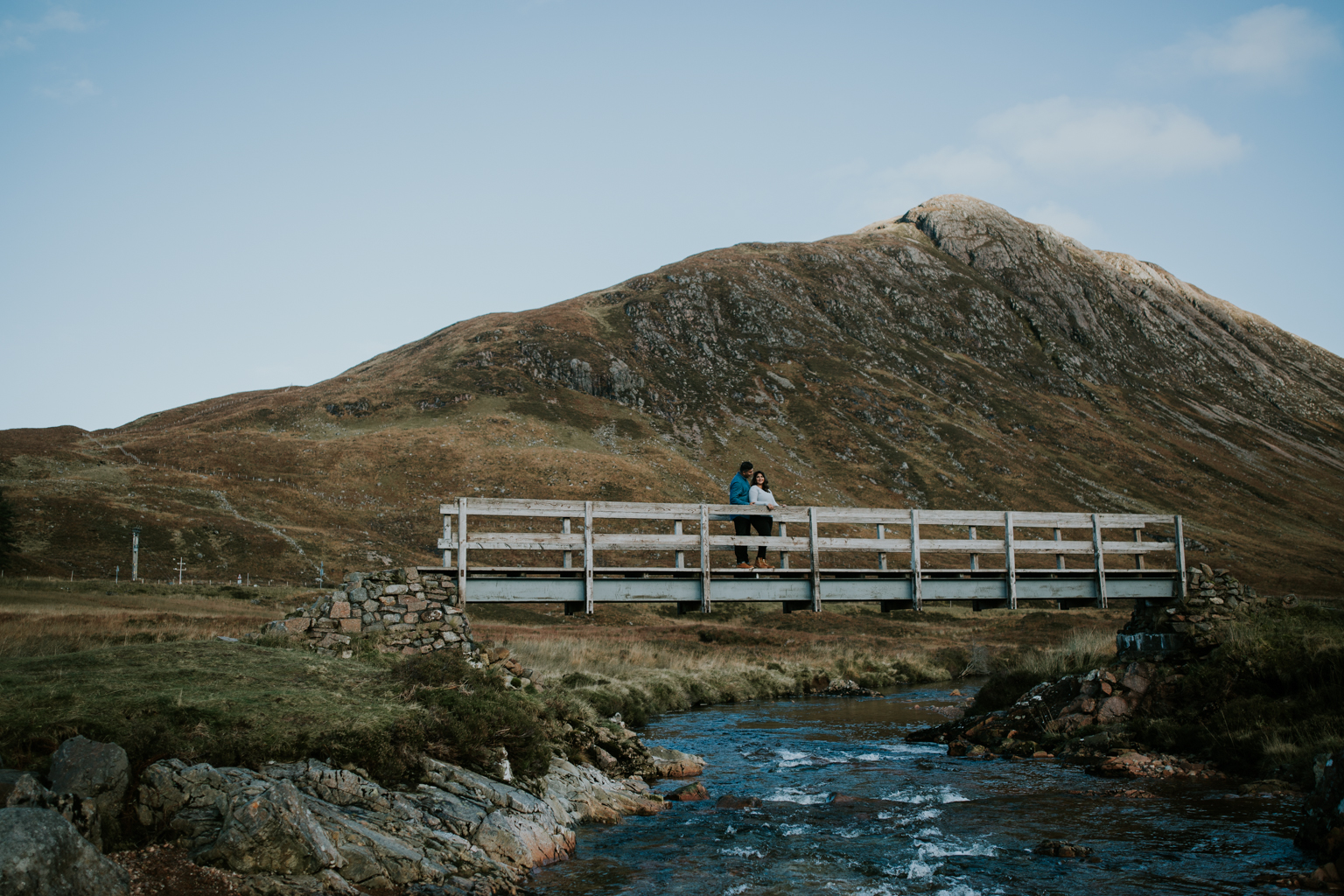 Couple is standing on a bridge in Glencoe, Scotland