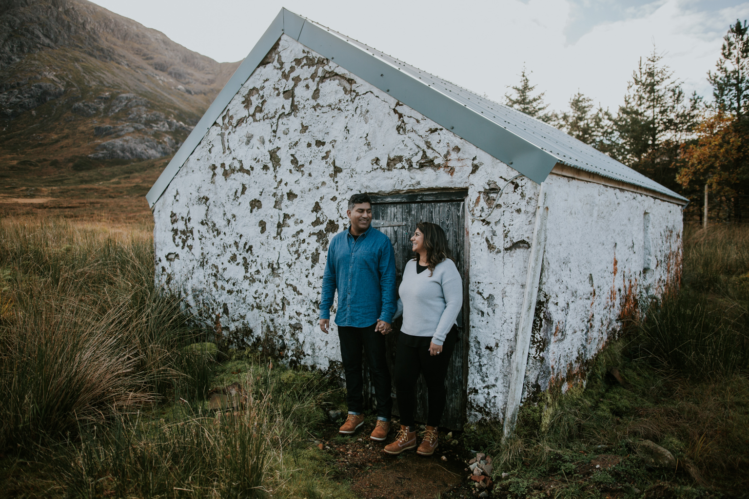 Couple is laughing next to the white house in Glencoe, Scotland.