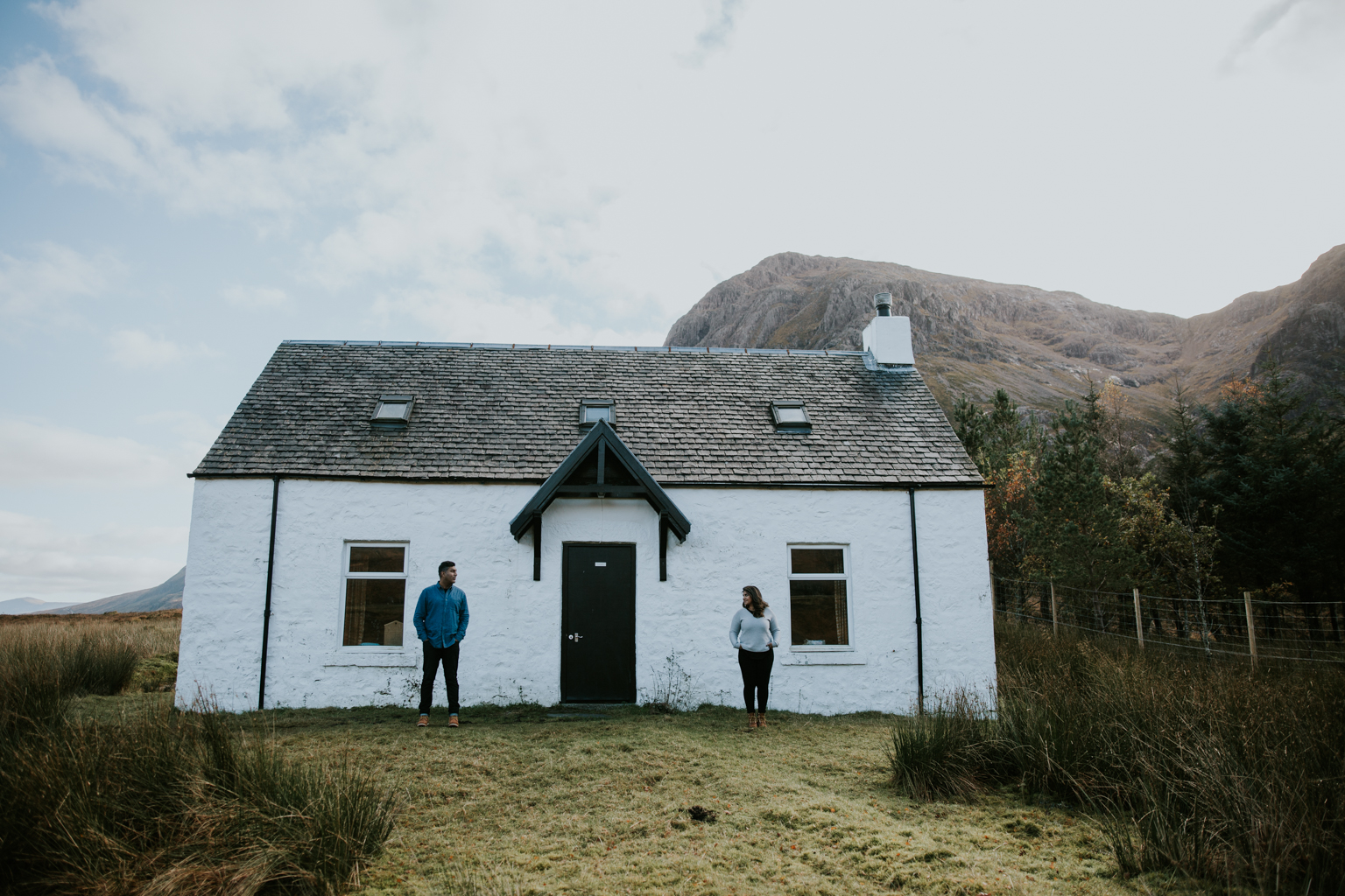 Couple is standing next to the white house in Glencoe, Scotland