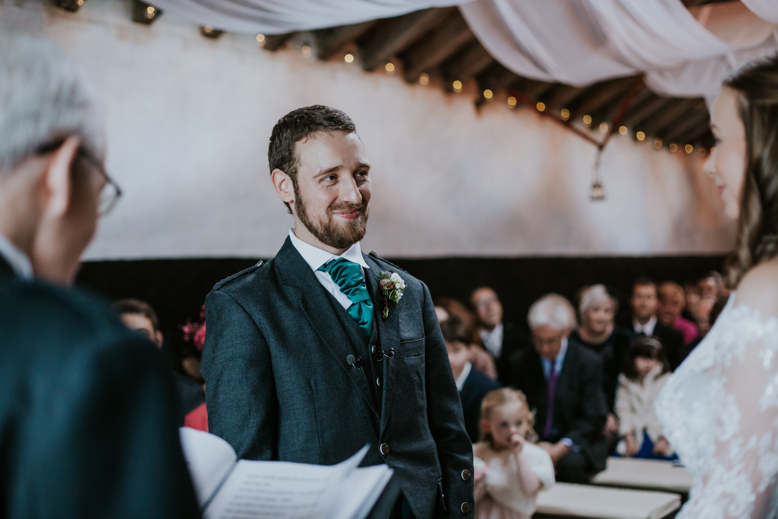 Groom is smiling and looking at the bride at the ceremony in Harelaw farm, Ayrshire