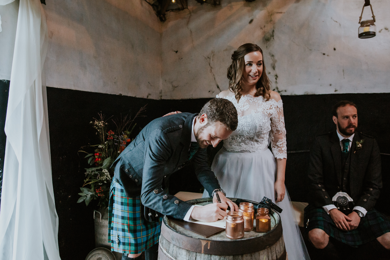 The groom is signing the marriage document. Harelaw farm wedding photographer