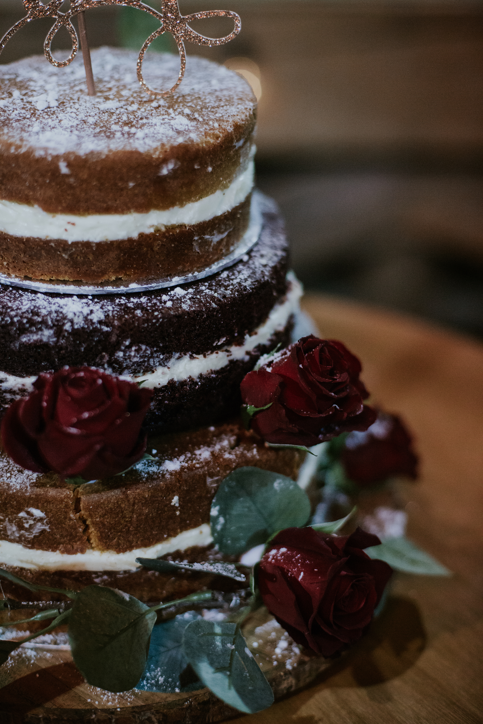 The stunning naked wedding cake with 3 tiers and roses as a decoration