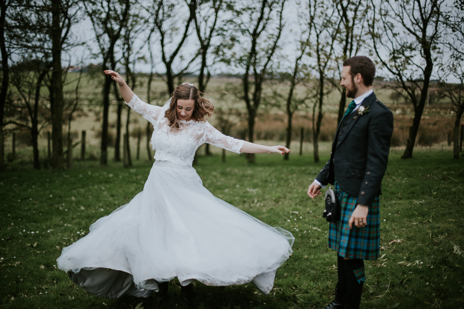 Bride is dancing in the field of Harelaw farm.