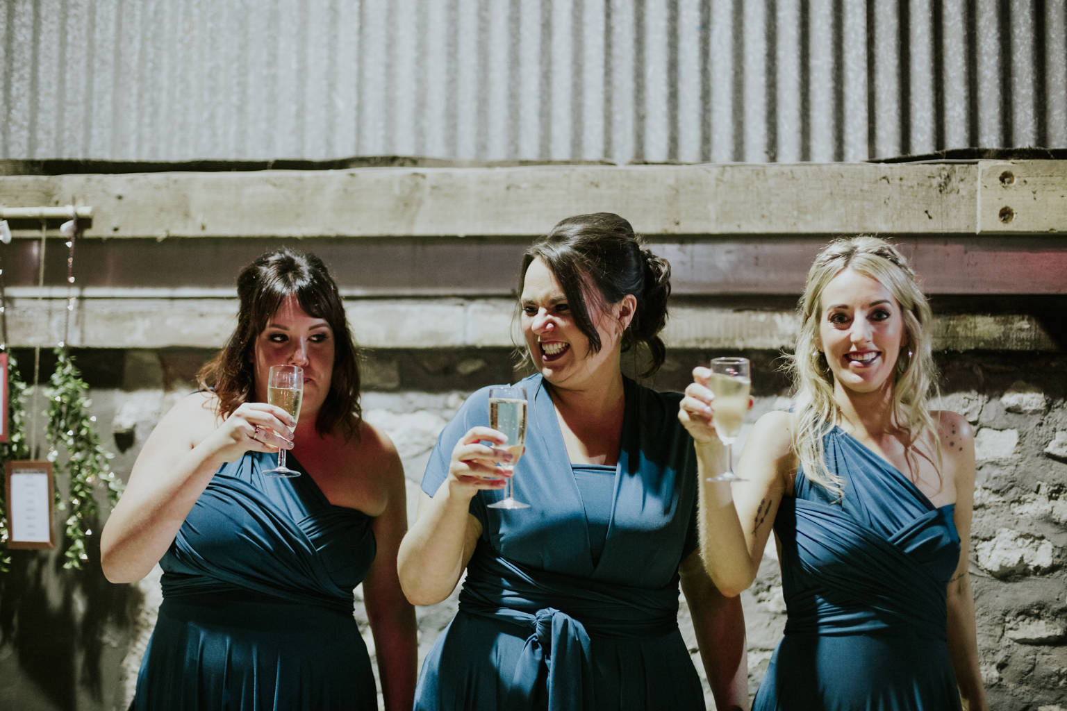 Bridesmaids are standing with smiling faces and champagne glasses at the wedding reception at Harelaw farm DIY wedding.
