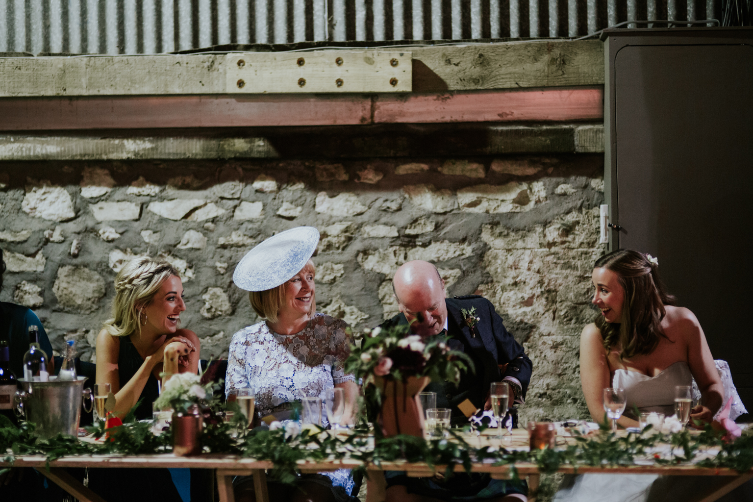 Bride, her mum, dad and bridesmaid are laughing at the wedding reception during the speech at Harelaw farm DIY wedding.